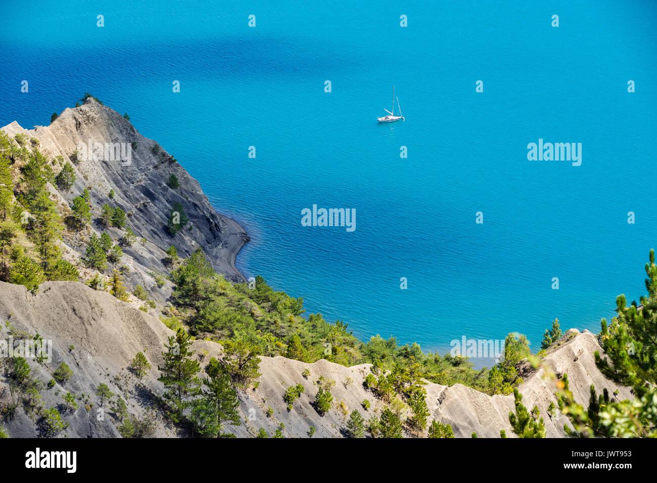 Le Lac de Serre-Ponçon en été avec de l'eau d'un bleu profond et bateau à voile. Hautes-Alpes, Région PACA, Alpes du Sud, France Photo Stock