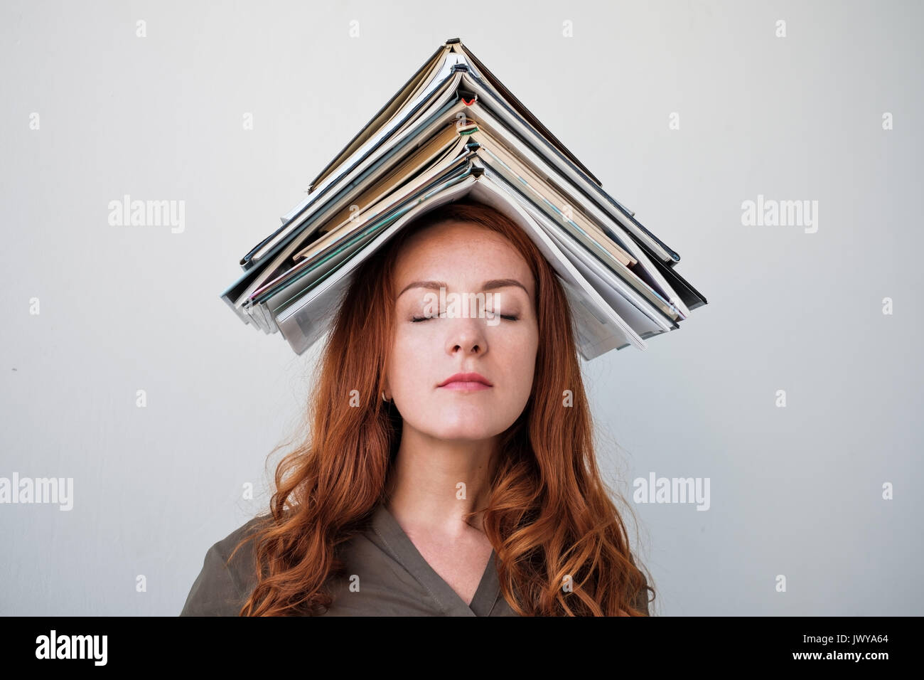Young woman balancing un livre sur sa tête Fond blanc Photo Stock