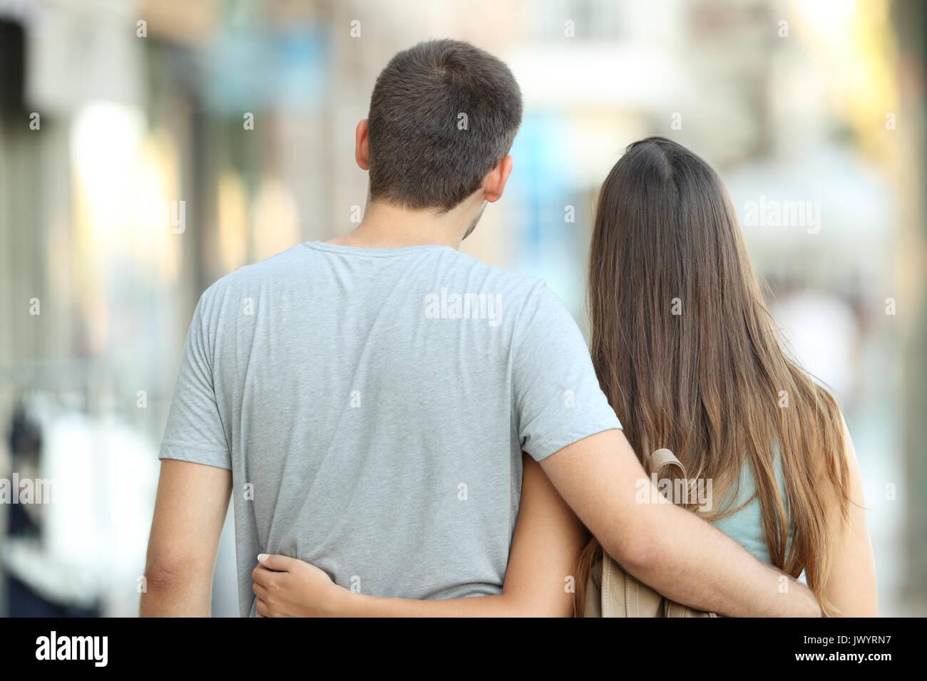 Vue arrière portrait of a casual couple marchant ensemble dans la rue Photo Stock