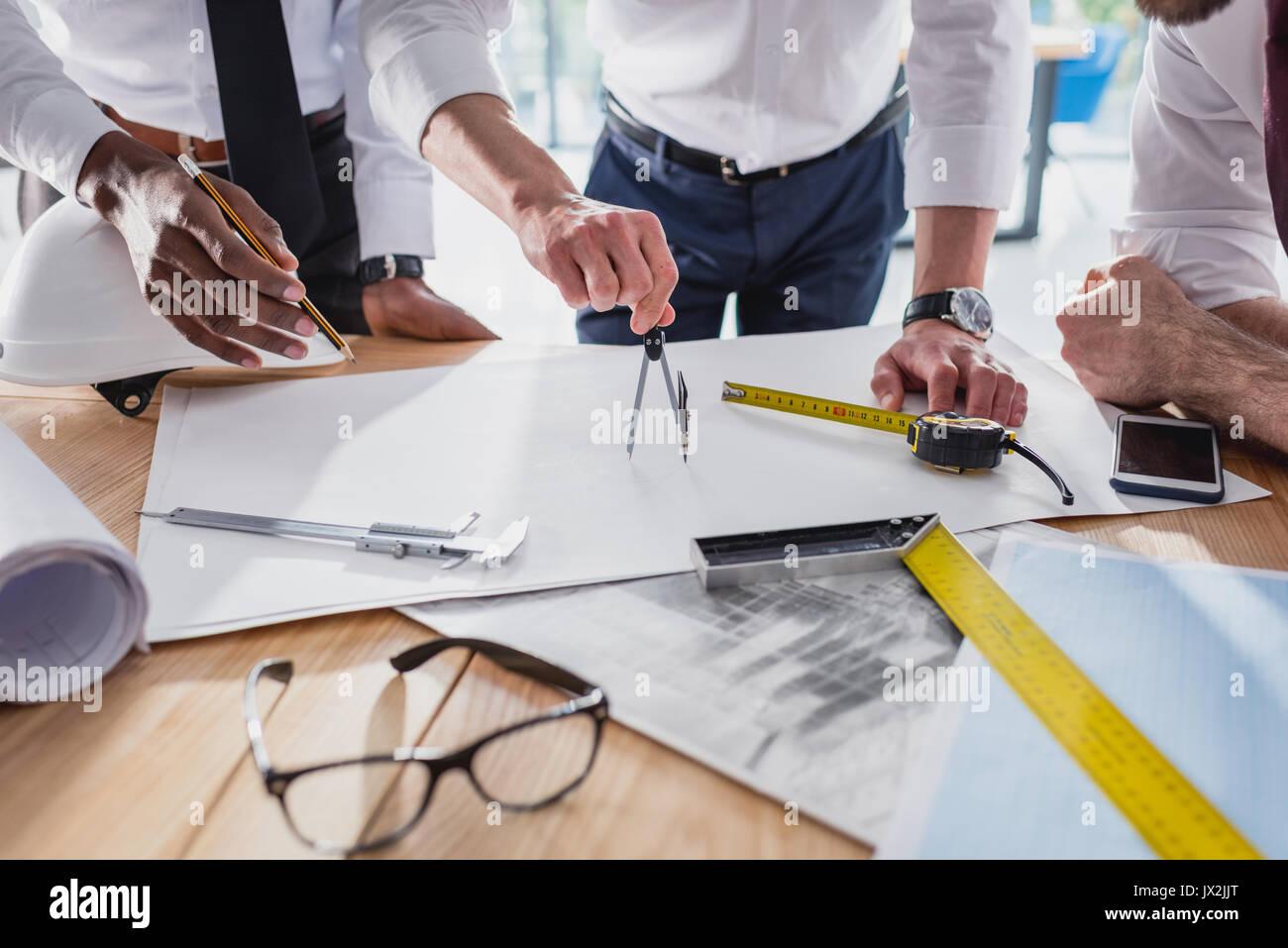 Vue partielle de l'équipe d'architectes travaillant sur le plan ensemble dans un bureau moderne Photo Stock