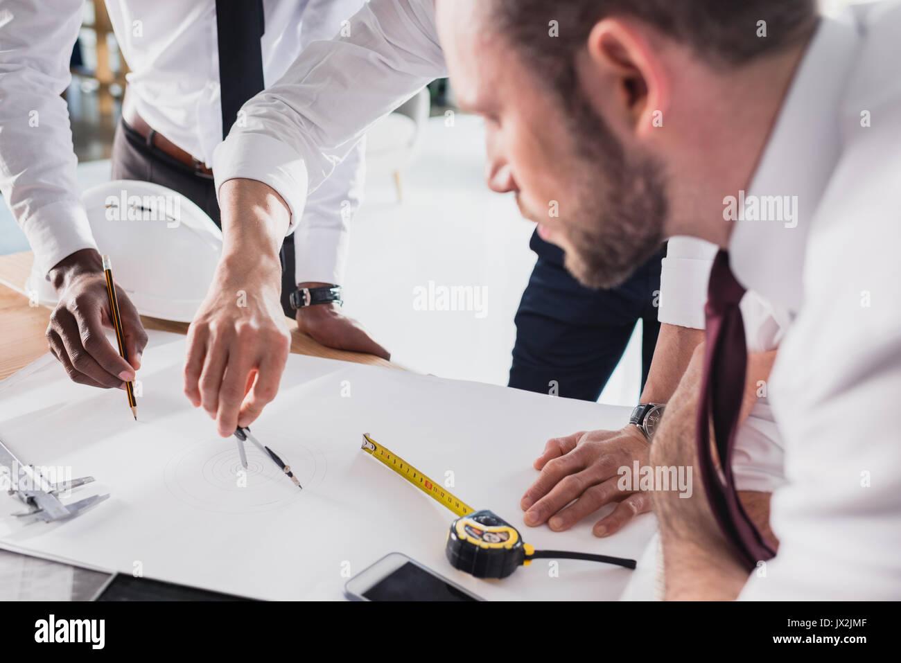 Équipe d'architectes travaillant sur le plan ensemble dans un bureau moderne Photo Stock