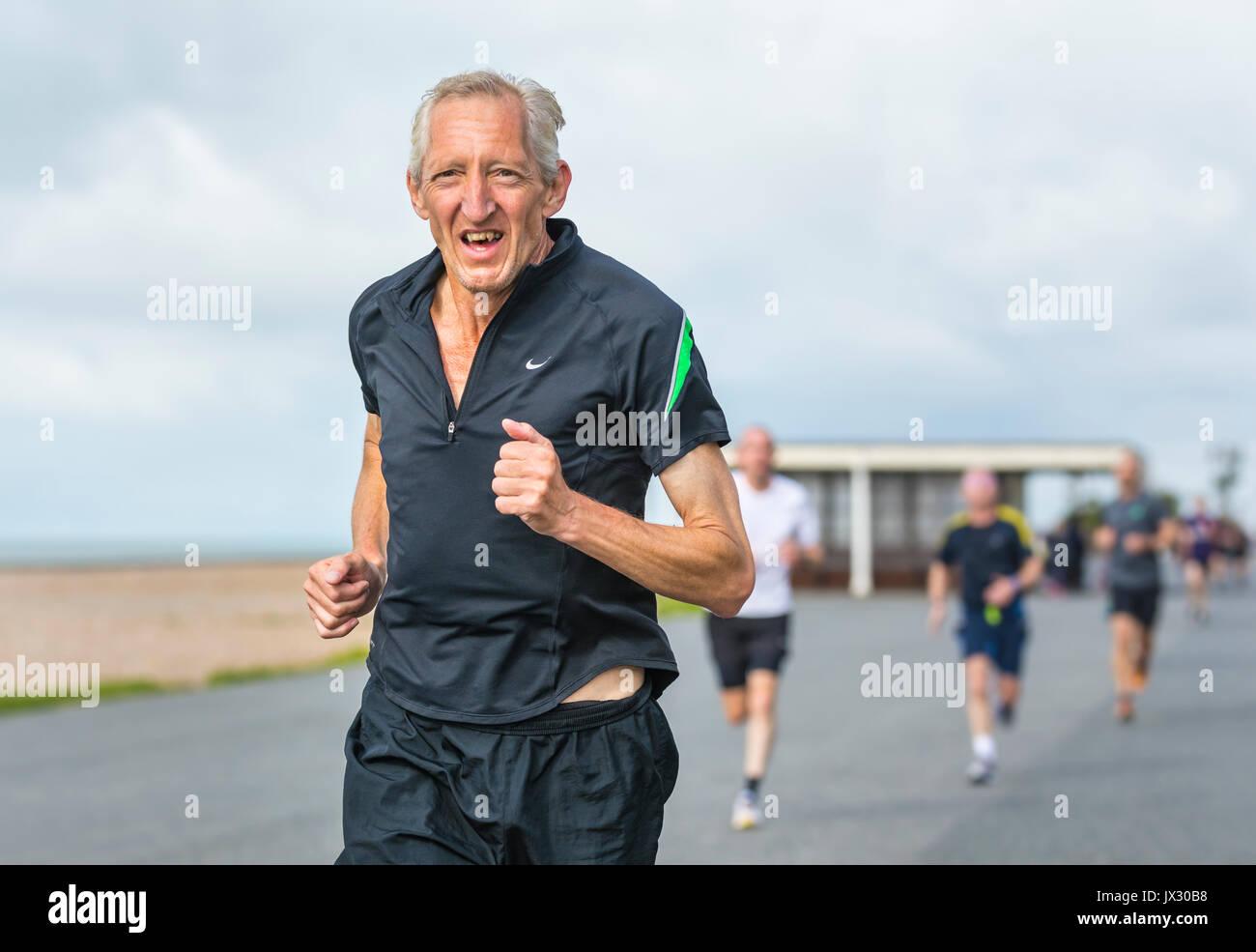 Un homme âgé s'exécutant sur la vitalité de l'événement hebdomadaire Parkrun à Worthing, West Sussex, Angleterre, Royaume-Uni. Photo Stock