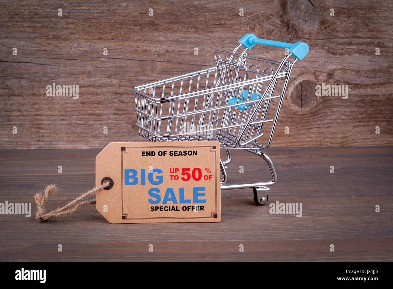 Grosse vente panier d'achat. avec une étiquette de prix vierge sur un fond de bois sombre. Photo Stock