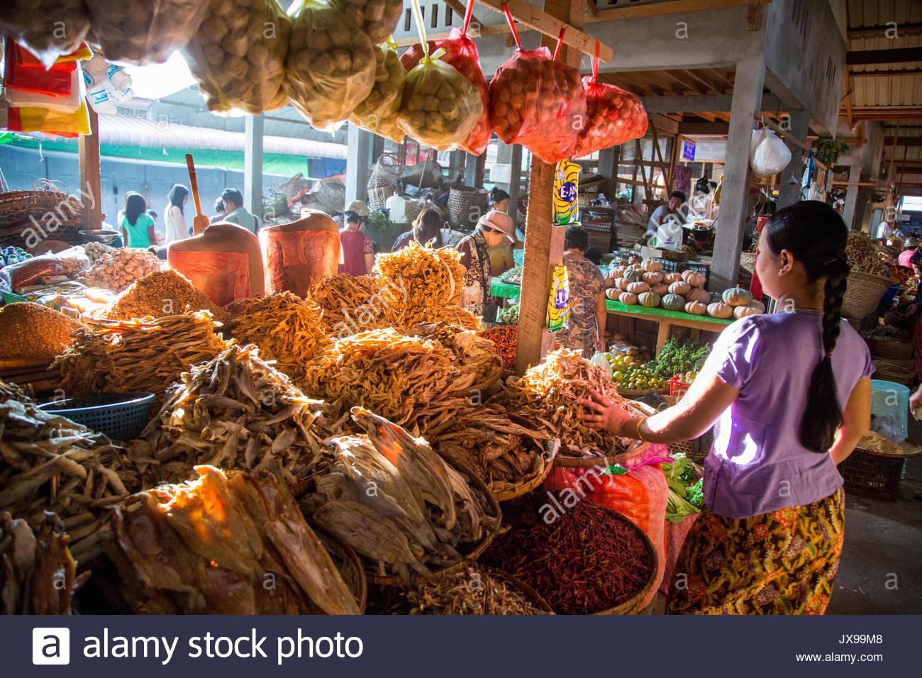 Une femme se trouve à côté d'un décrochage du vendeur rempli d'aliments déshydratés. Photo Stock