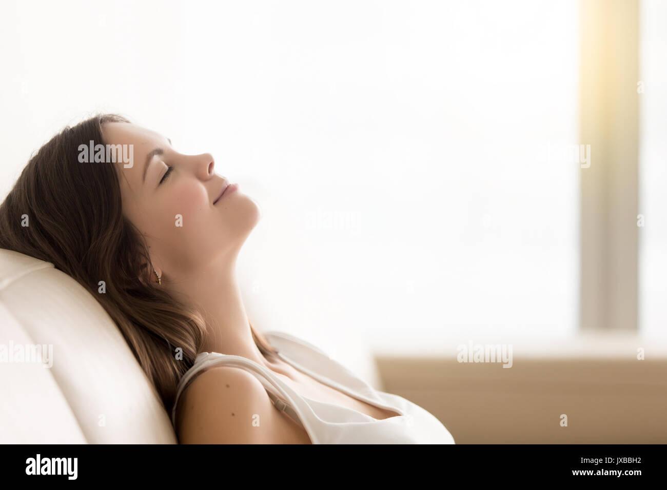 Young woman enjoying détendue reste sur un canapé confortable, une savs copie Photo Stock