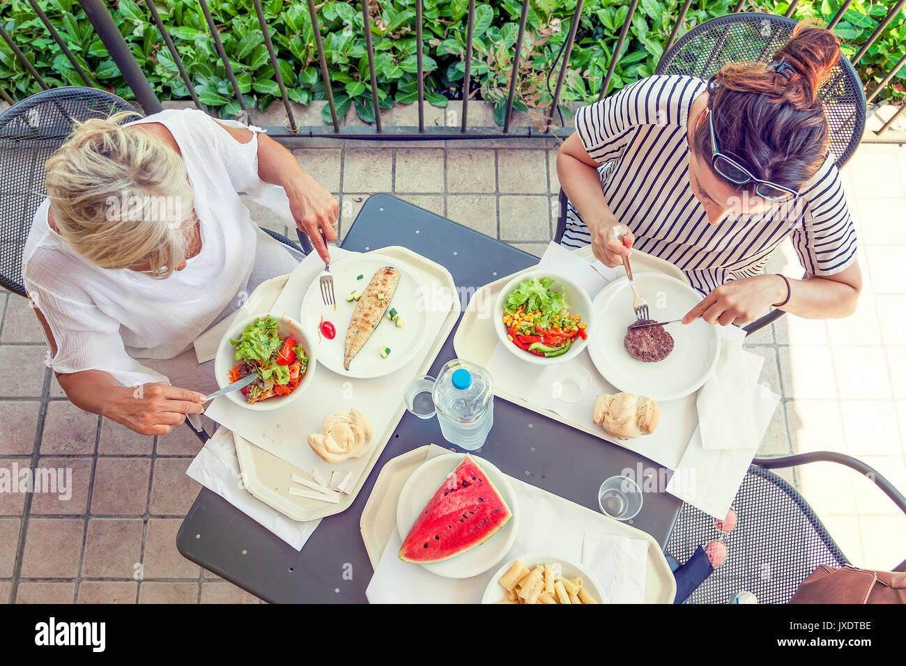Maman moderne et jeune fille au dîner assis à la table dans un parc aquatique sur l'été. Concept de belles personnes s'amusant en été Photo Stock