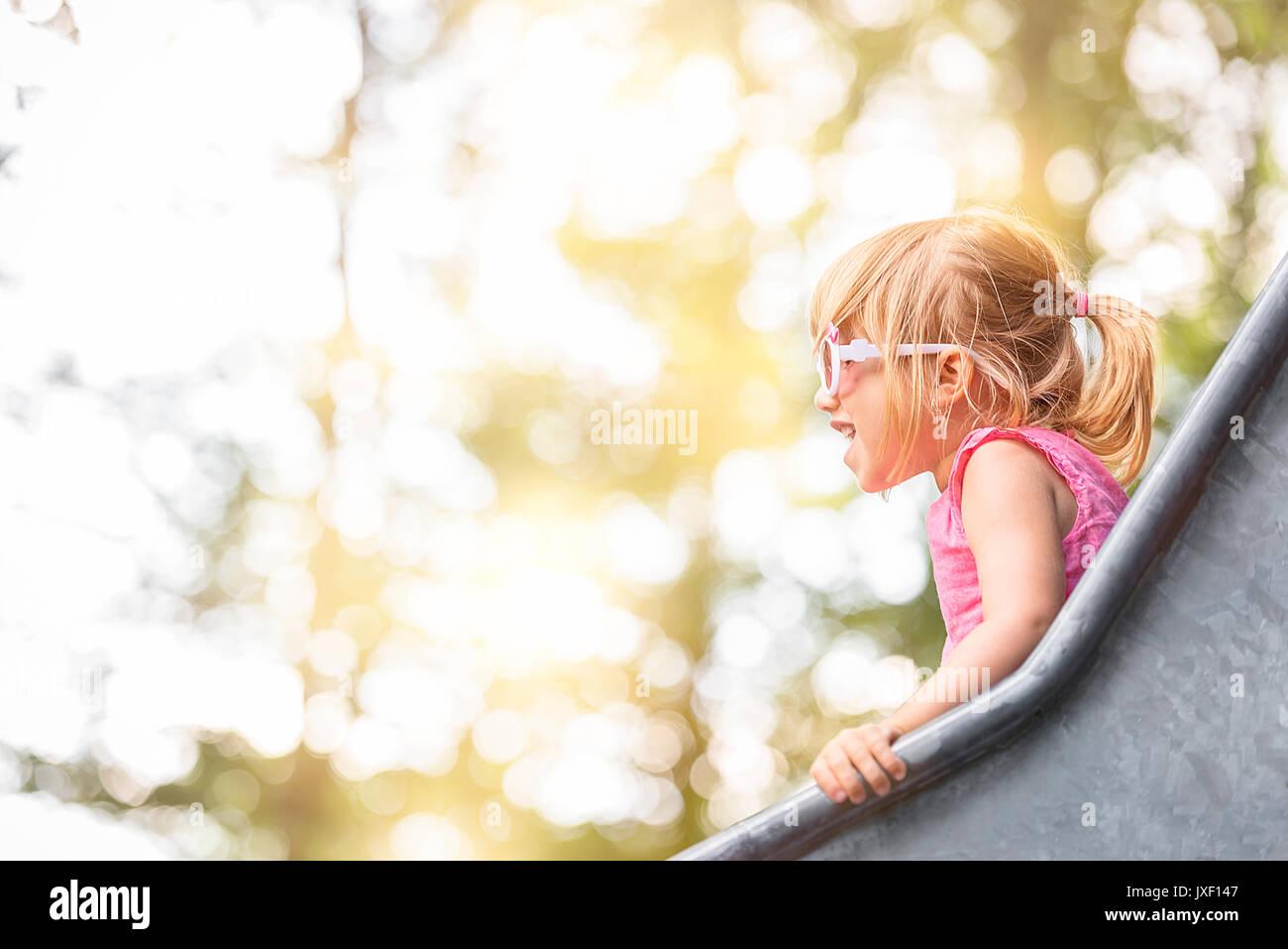 Image en gros plan avec une petite fille s'amusant sur une diapositive à partir d'une aire de jeux, sur une journée ensoleillée. Photo Stock