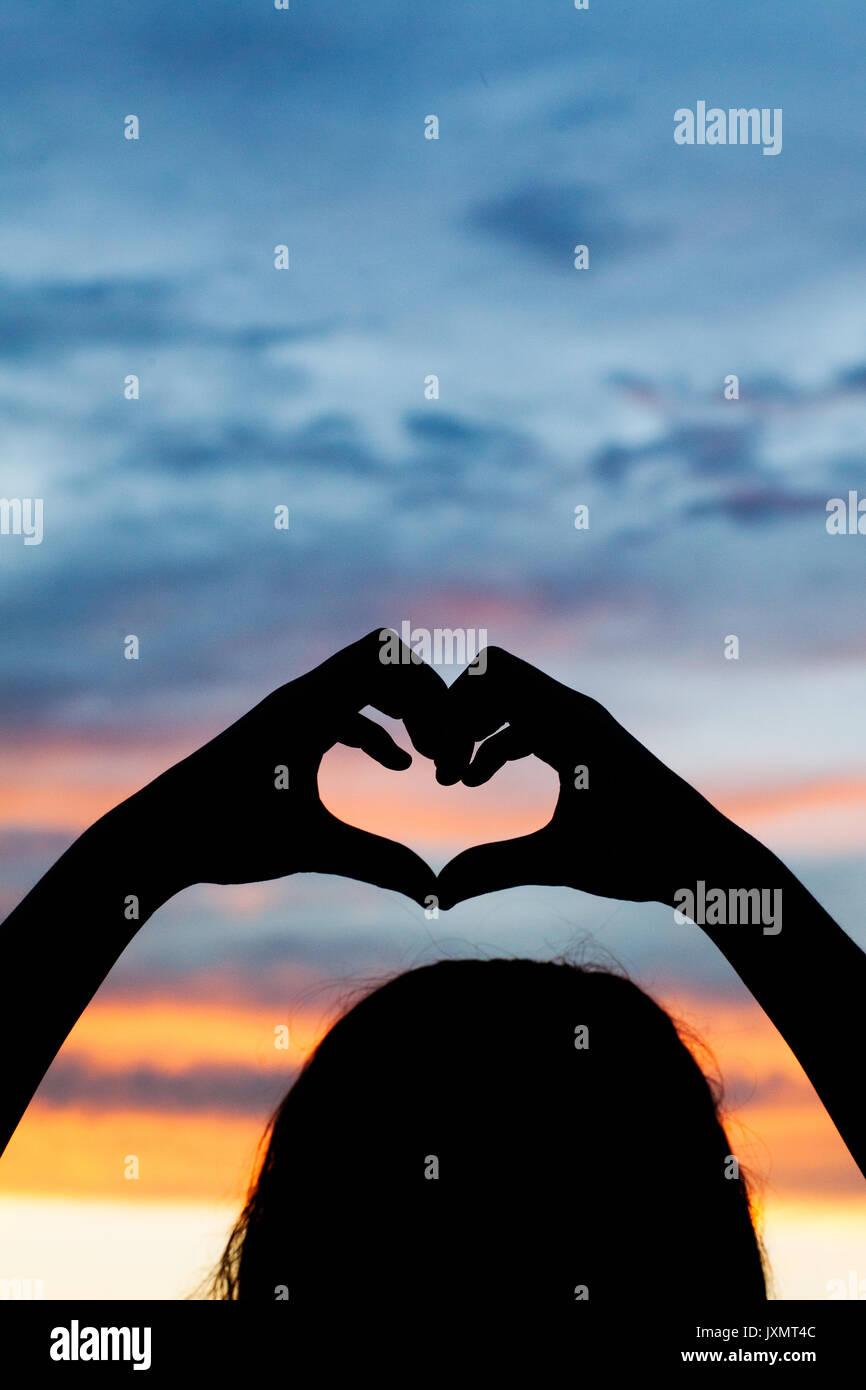 silhouette de jeune fille faire coeur avec ses mains contre ciel dramatique banque d 39 images. Black Bedroom Furniture Sets. Home Design Ideas