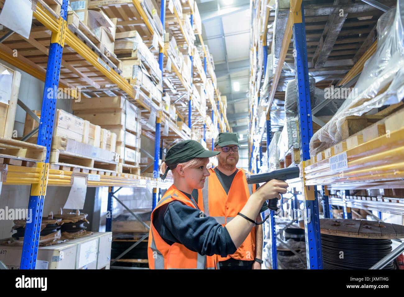 Les travailleurs de stockage des pièces dans la numérisation des œuvres de train warehouse Photo Stock