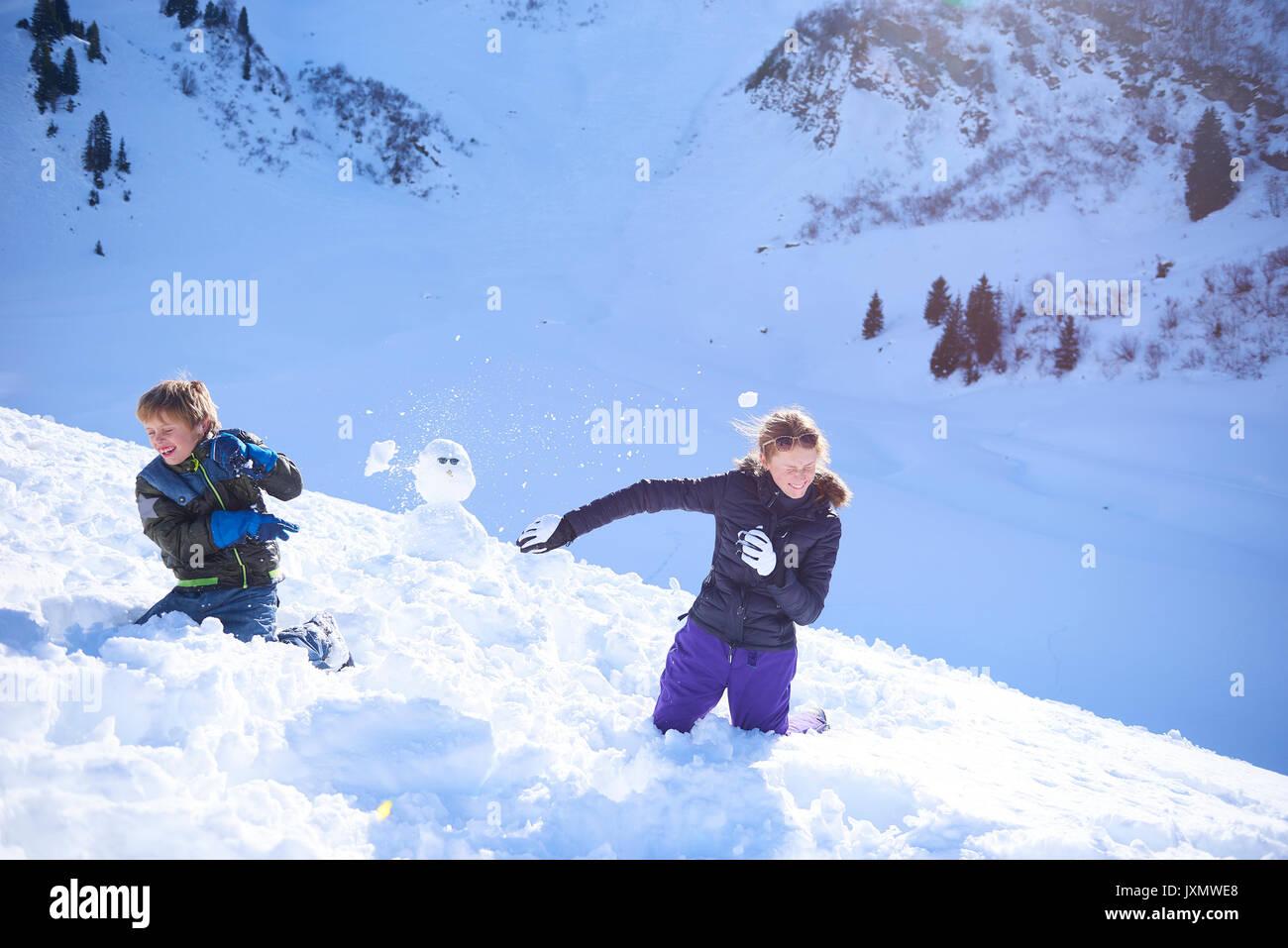 Frères et sœurs ayant snow ball fight, Hintertux, Tyrol, Autriche Photo Stock