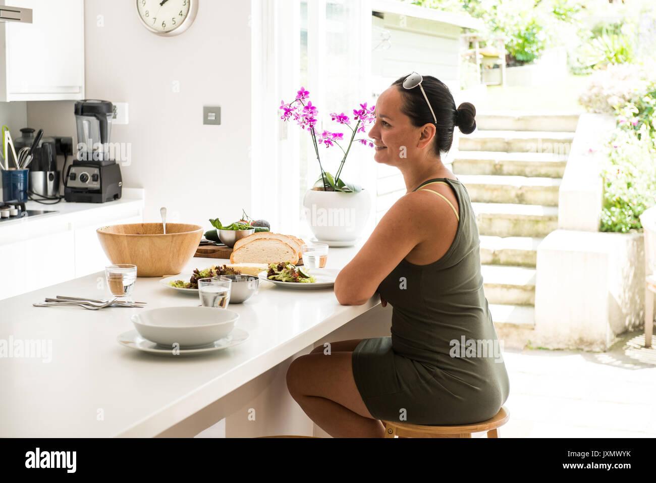Femme assise à la cuisine île bénéficiant d'un déjeuner salade Photo Stock