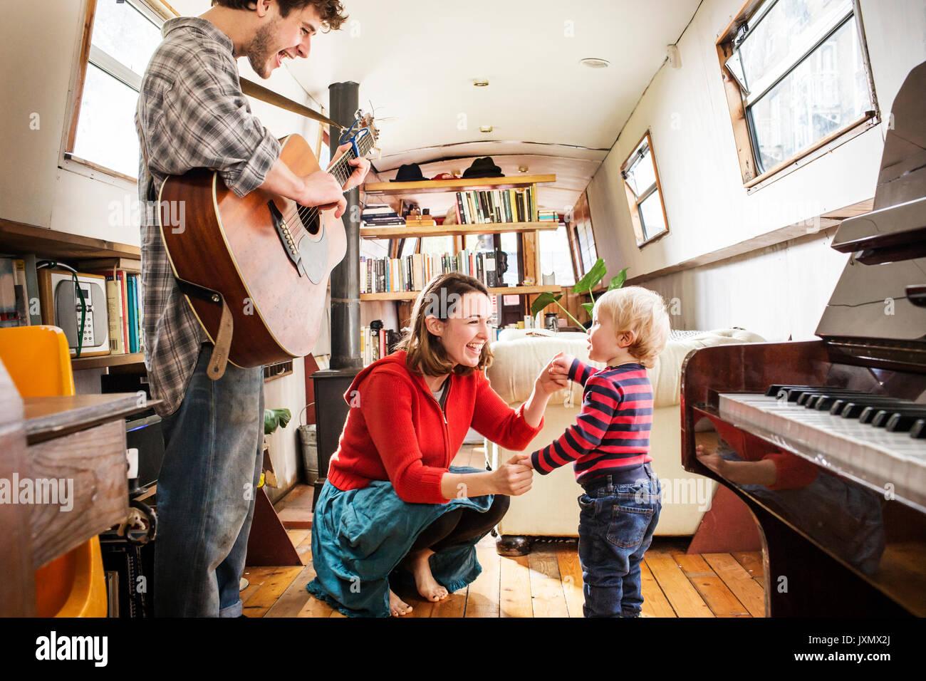 Famille avec bébé garçon vivant sur barge à jouer de la guitare et de la danse Photo Stock