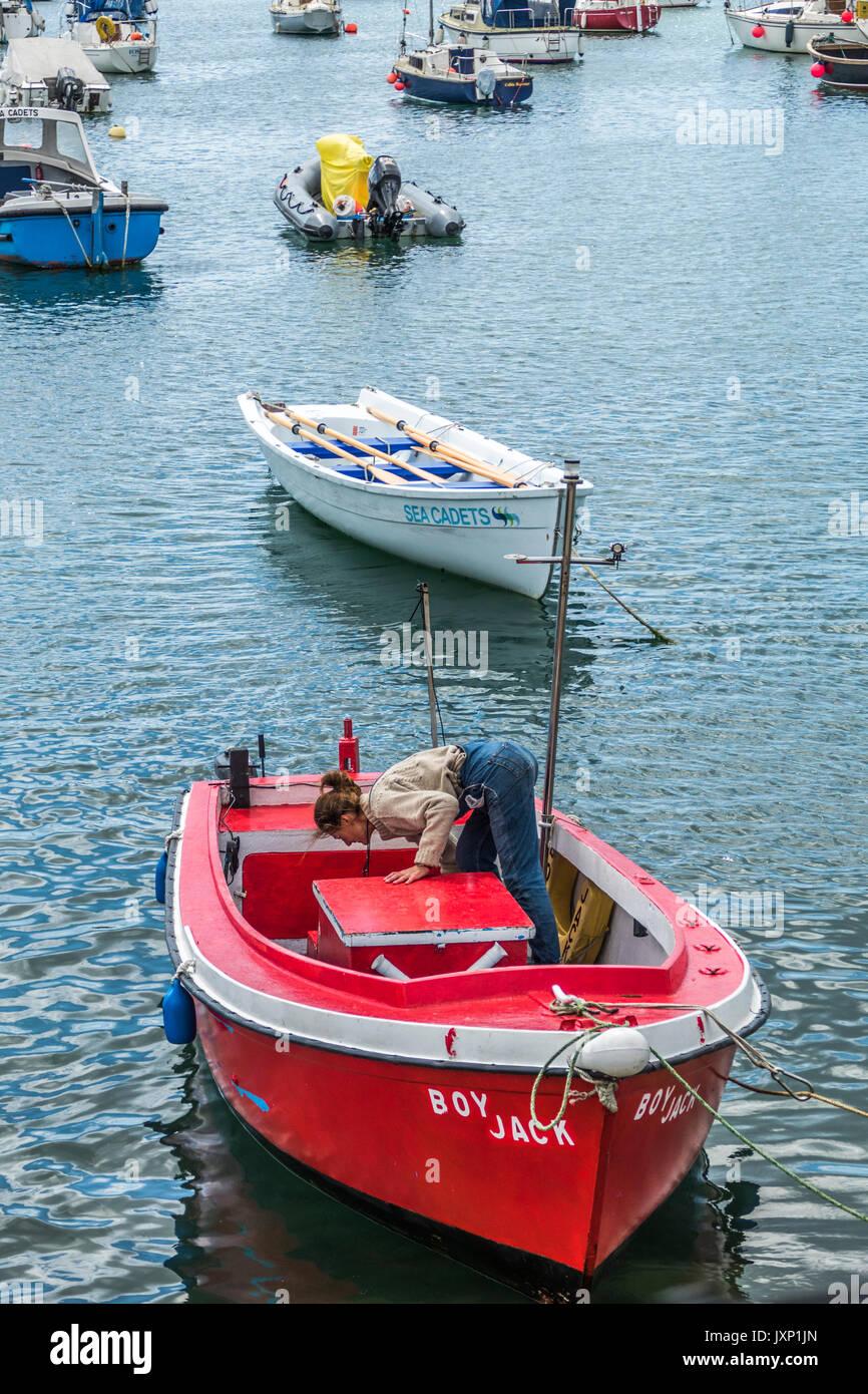 Une femme d'âge moyen, seul dans une petite embarcation à moteur qu'elle est sur le point de Moor, parmi d'autres bateaux dans le port de Penzance, Cornwall, England, UK. Photo Stock