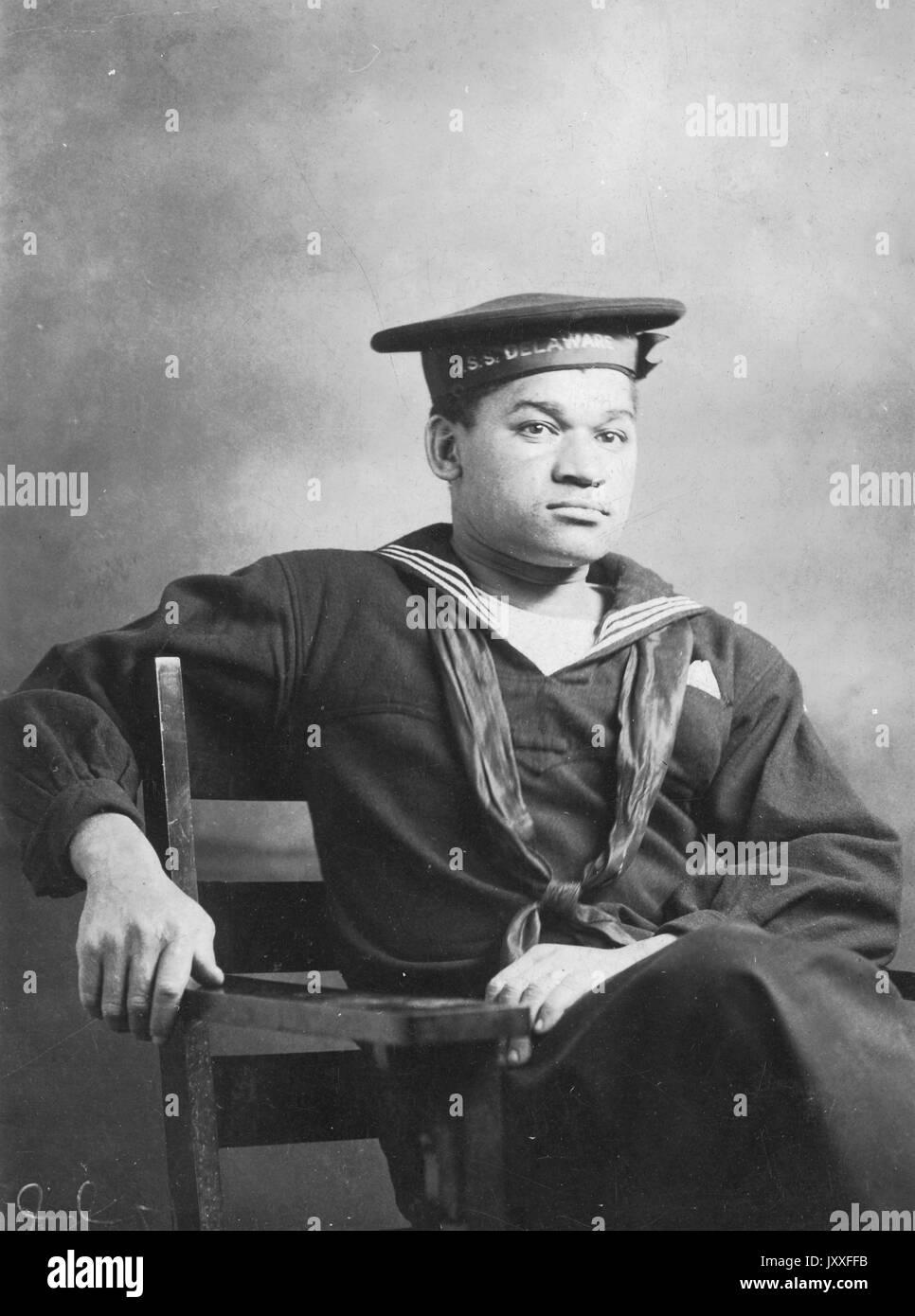 Portrait de trois-quarts un afro-américain première guerre mondiale us navy marin, assis, en uniforme, expression faciale neutre, 1920. Photo Stock