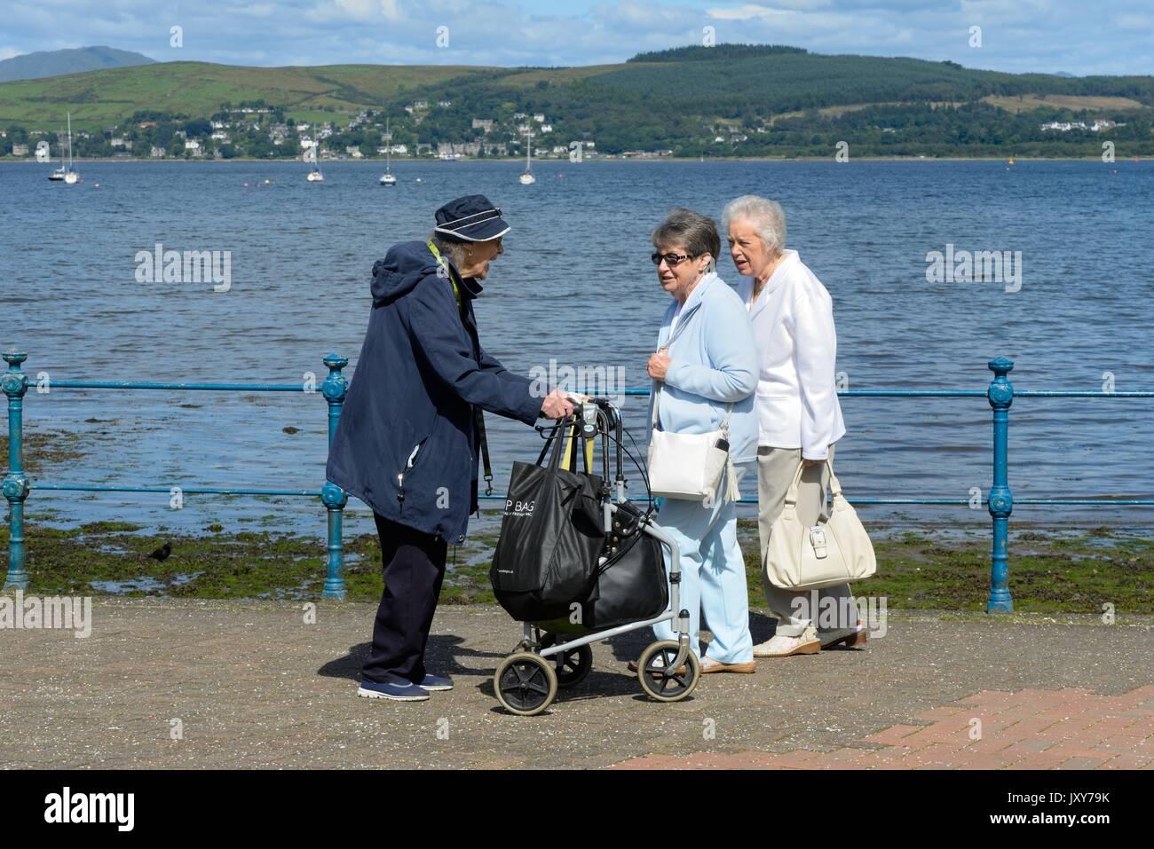 Trois retraités rencontrez en marchant sur la promenade au bord de la baie de Cardwell, Gourock, Ecosse, Royaume-Uni Photo Stock