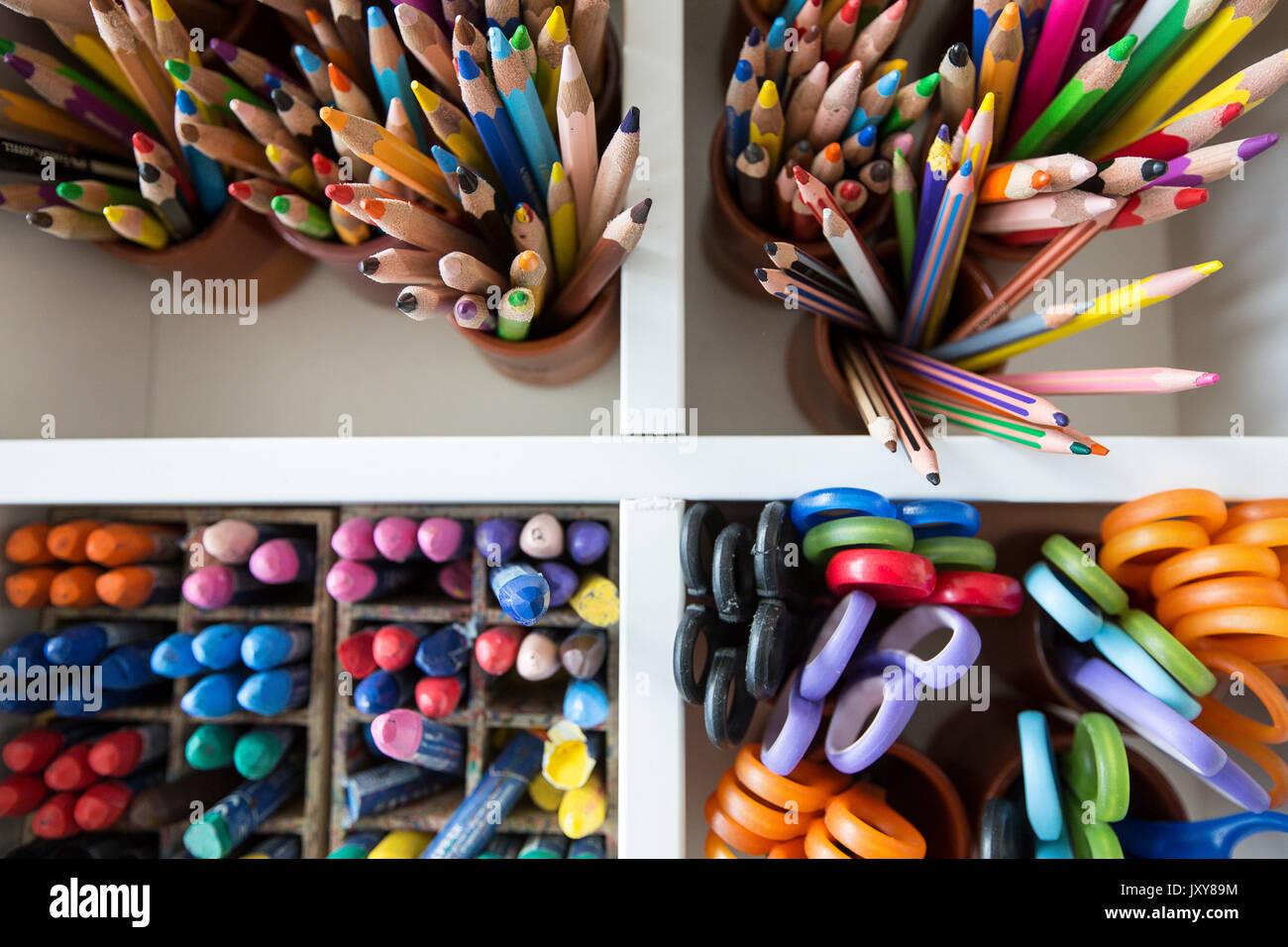 L'enseignement primaire, élémentaire ou de l'école maternelle. Crayons de couleur, pastel et des ciseaux dans une pièce de mobilier blanc Banque D'Images