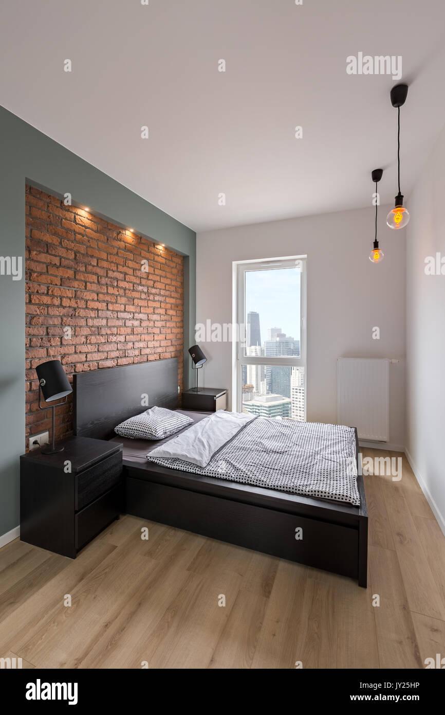 Chambre en mezzanine avec lit double et mur de brique rouge Banque D ...