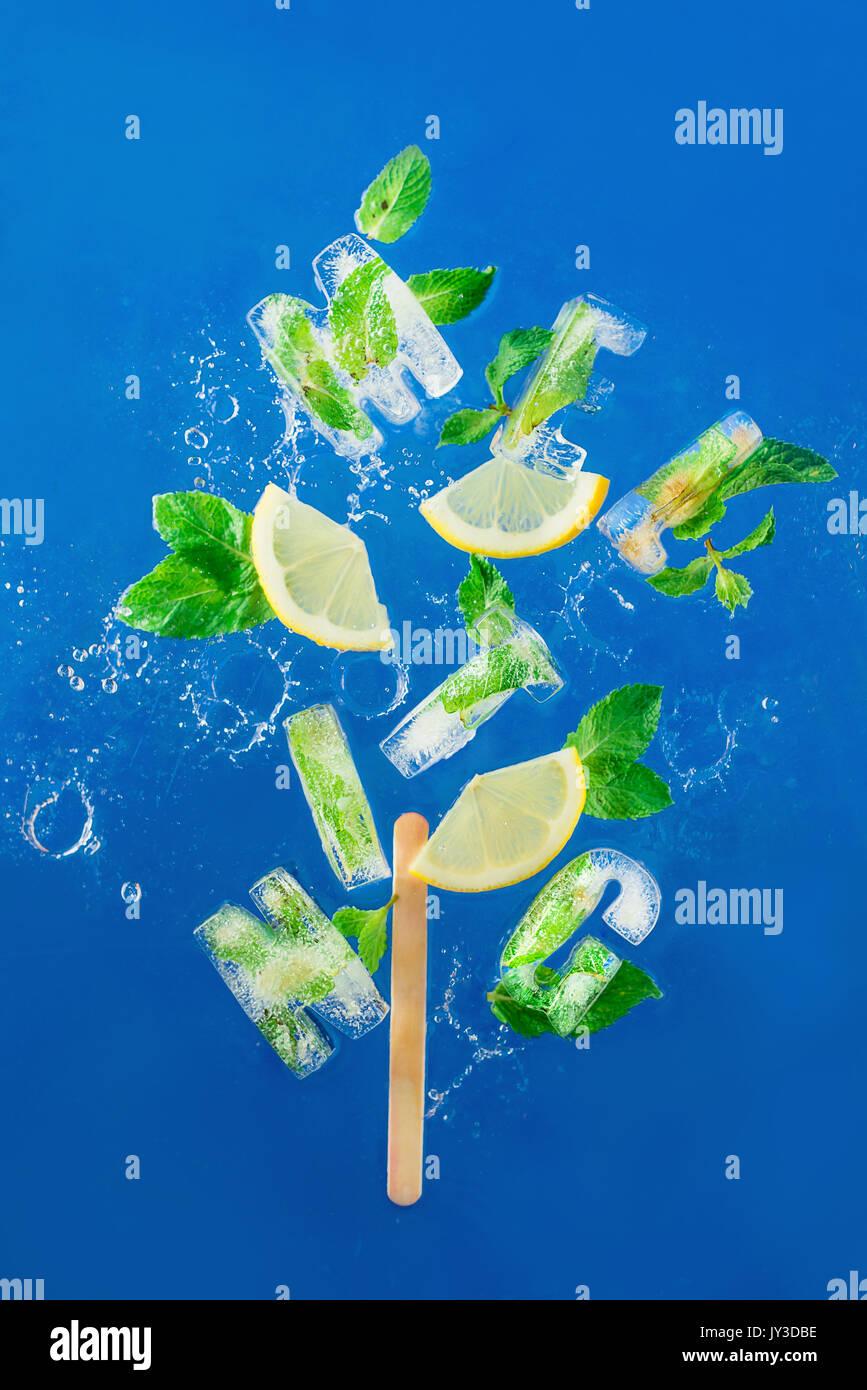 Ice Cube congelé un lettrage en feuilles de menthe, de tranches de citron et d'oranges sur un fond bleu avec les projections d'eau. texte dit de fondre. Photo Stock