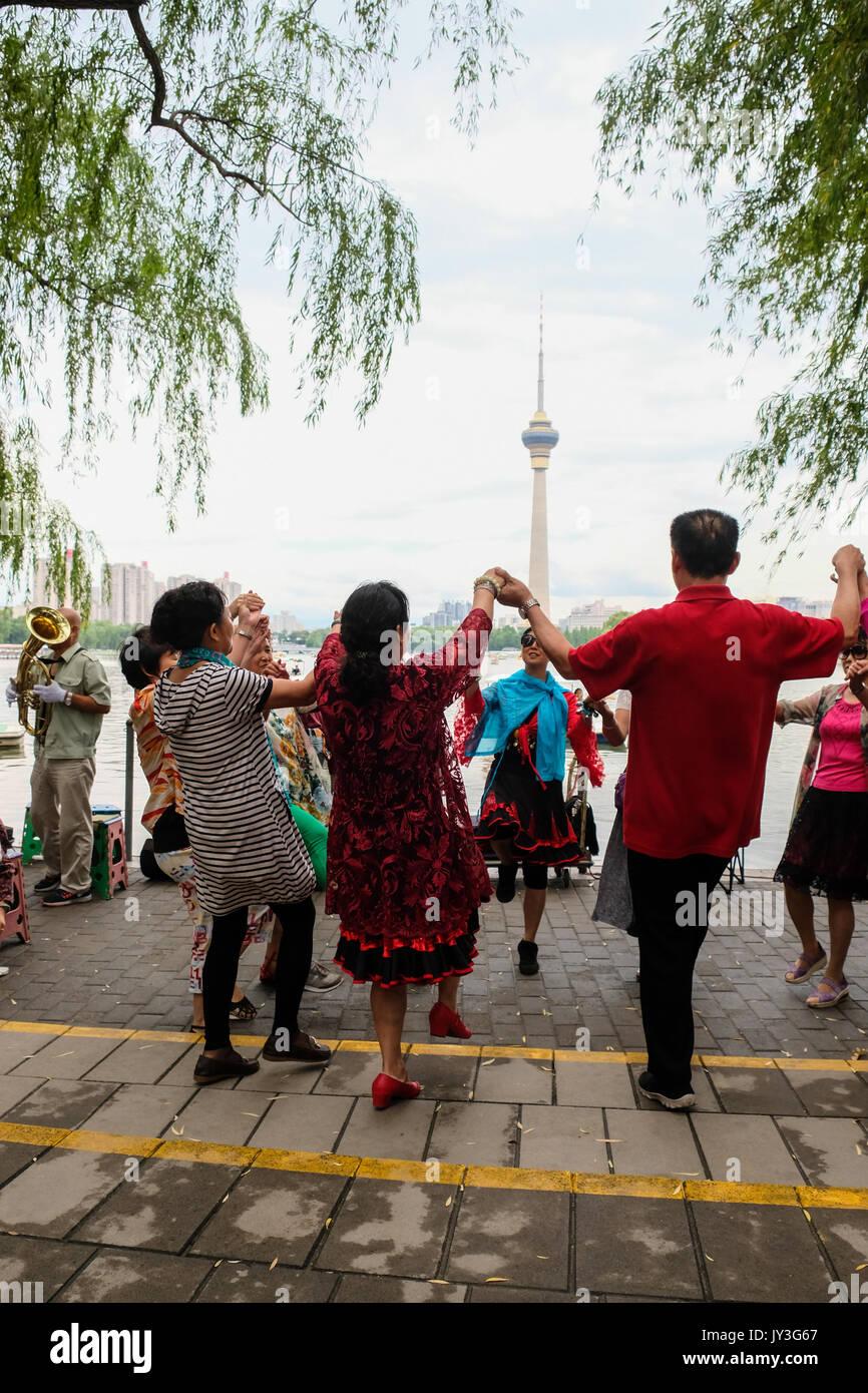Chinois retraités hommes et femmes se tenant la main et dansant dans le parc Photo Stock