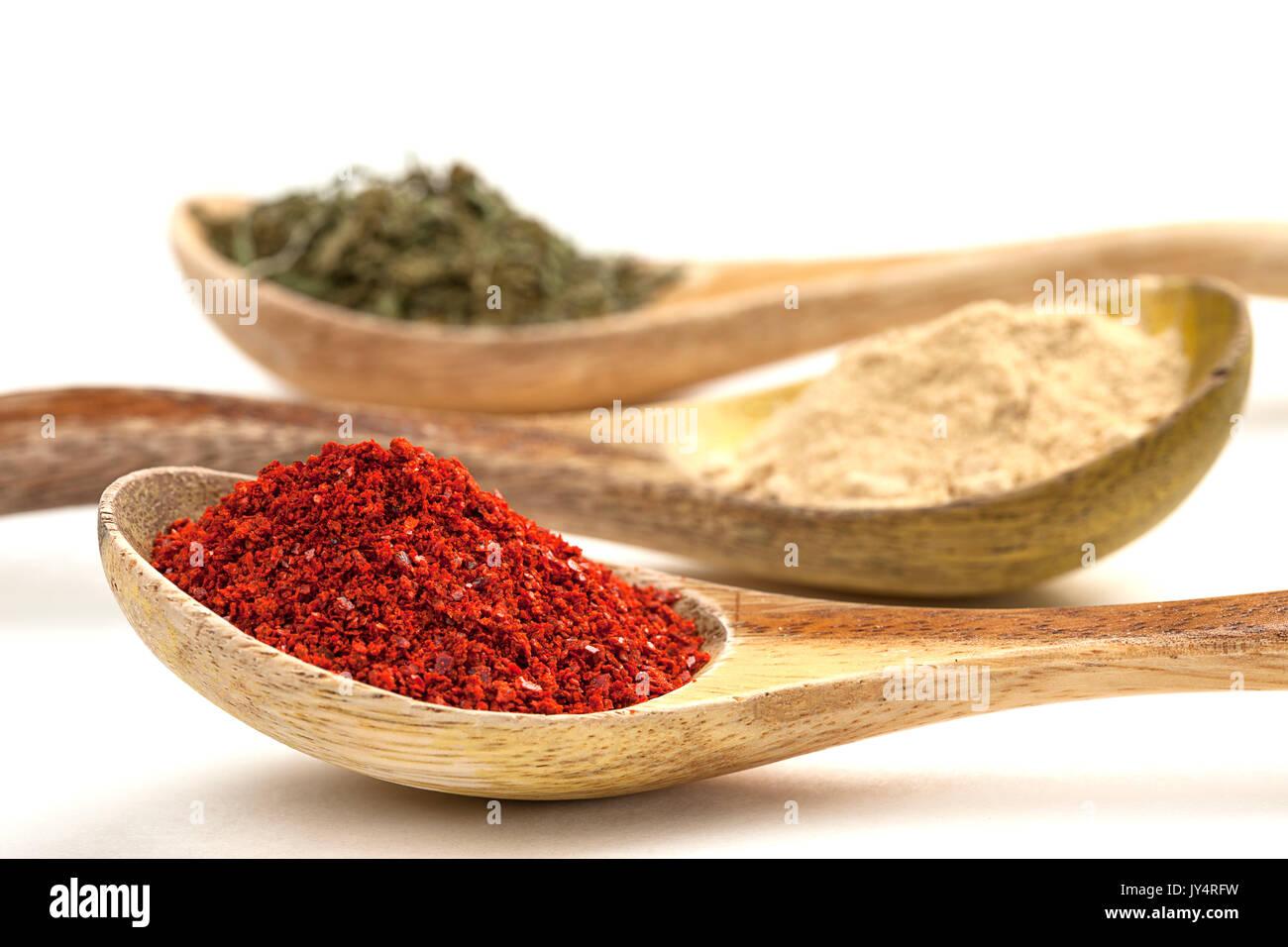 Un gros plan de cuillères en bois remplis de poudre de poivre rouge, ail en poudre, et les feuilles de basilic. Photo Stock