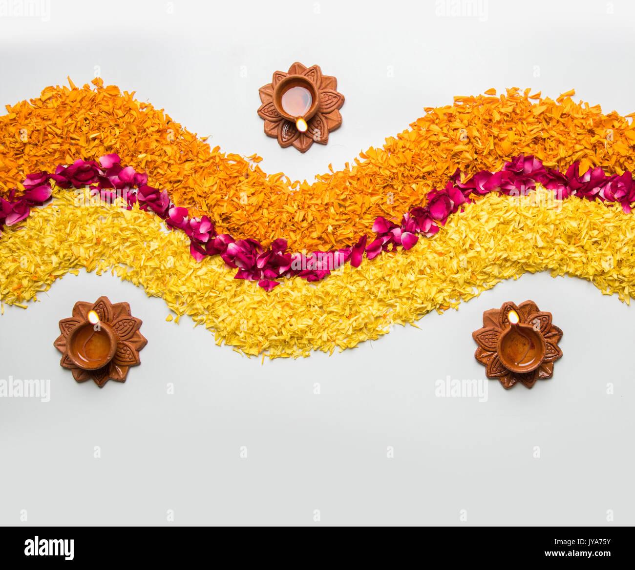 Rangoli fleur pour Diwali ou pongal fait à l'aide de l'œillet ou zendu fleurs et pétales de rose rouge sur fond Banque D'Images