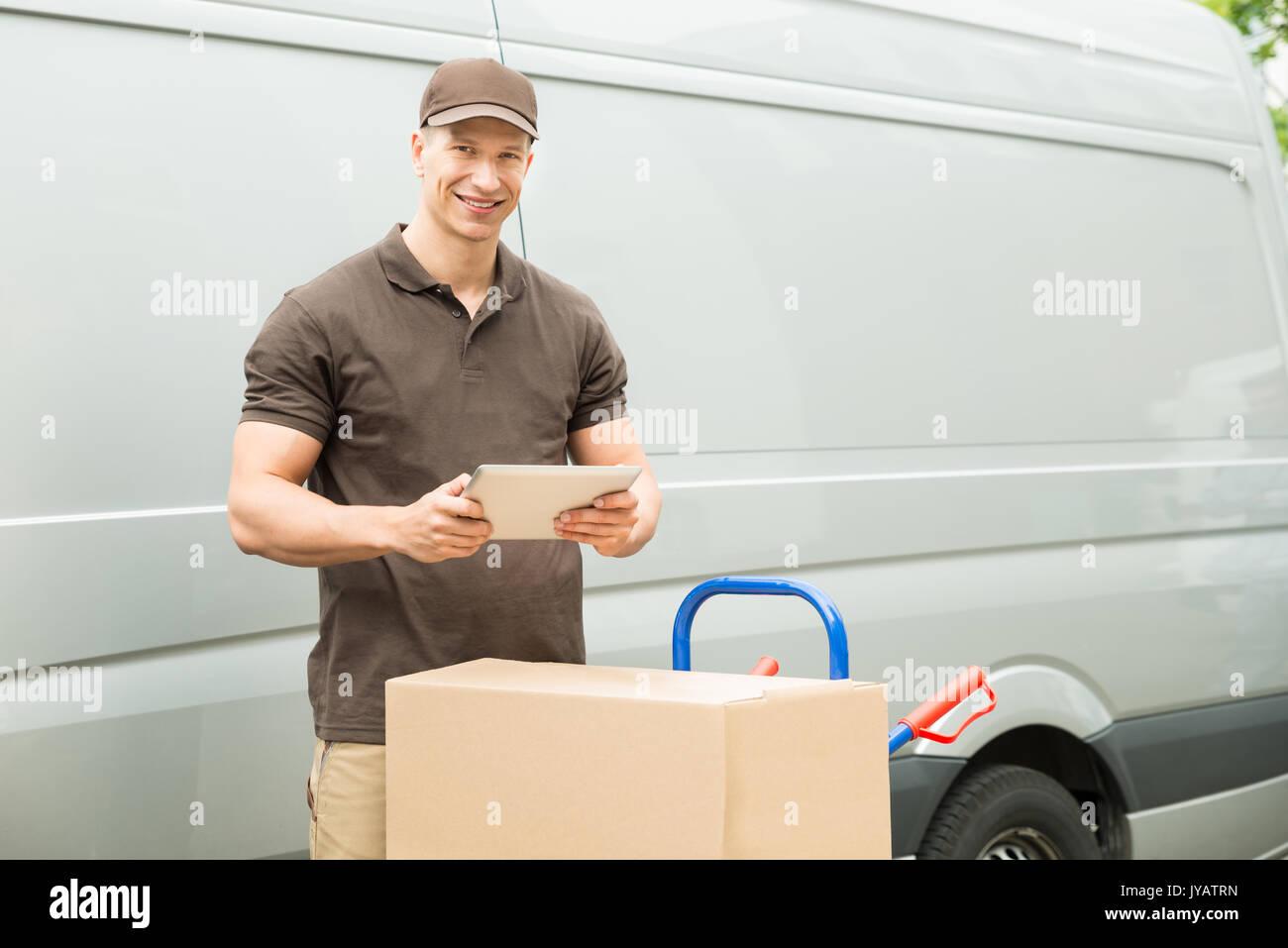 Les jeunes professionnels Delivery Man with Digital Tablet et boîtes de carton Photo Stock