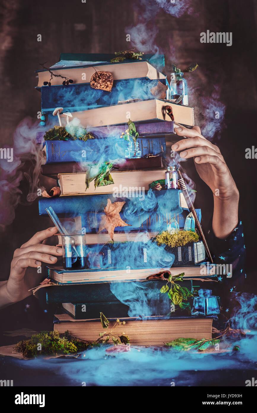 Une pile de livres magiques avec les mains de l'assistant. Photo Stock