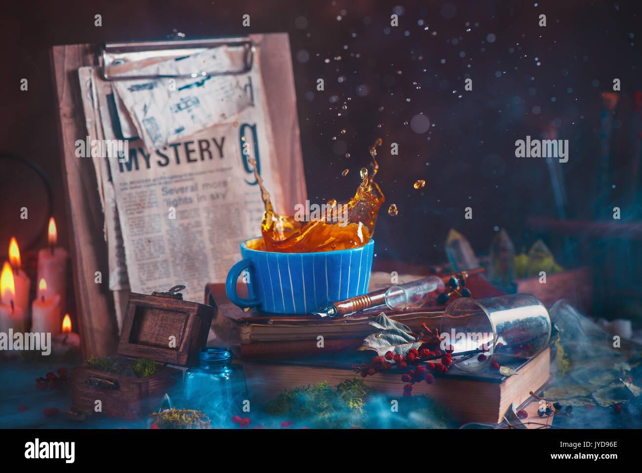 Plateau splash dans une tasse en céramique sur un fond de bois avec des bougies, du mystère, des livres, des clips journal feuilles et gouttes d'eau. moss. bokeh stil magique sombre Photo Stock