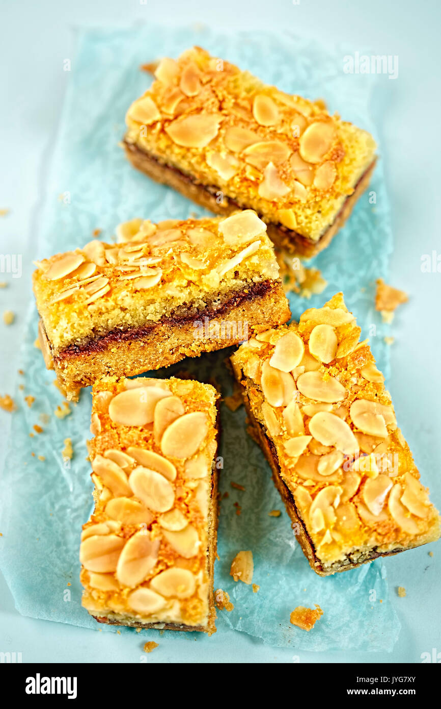 Bien cuire framboise teacake with almond flakes sur surface bleu Photo Stock