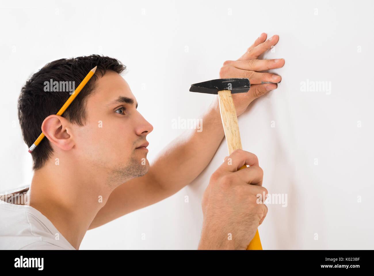 Vue latérale du jeune homme hammering nail sur mur blanc à la maison Banque D'Images