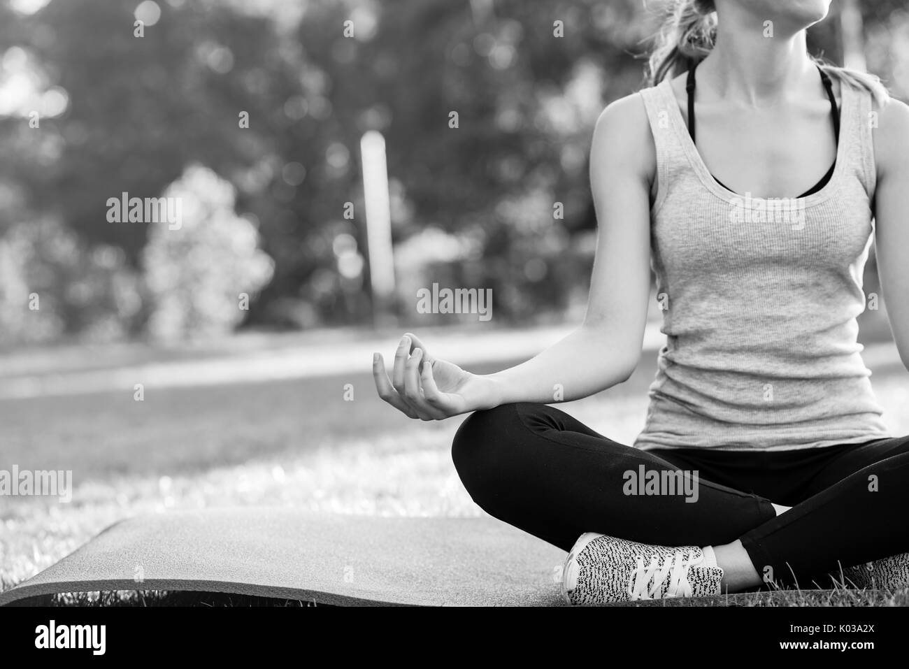 Jeune femme pratiquant le yoga en plein air au parc Photo Stock