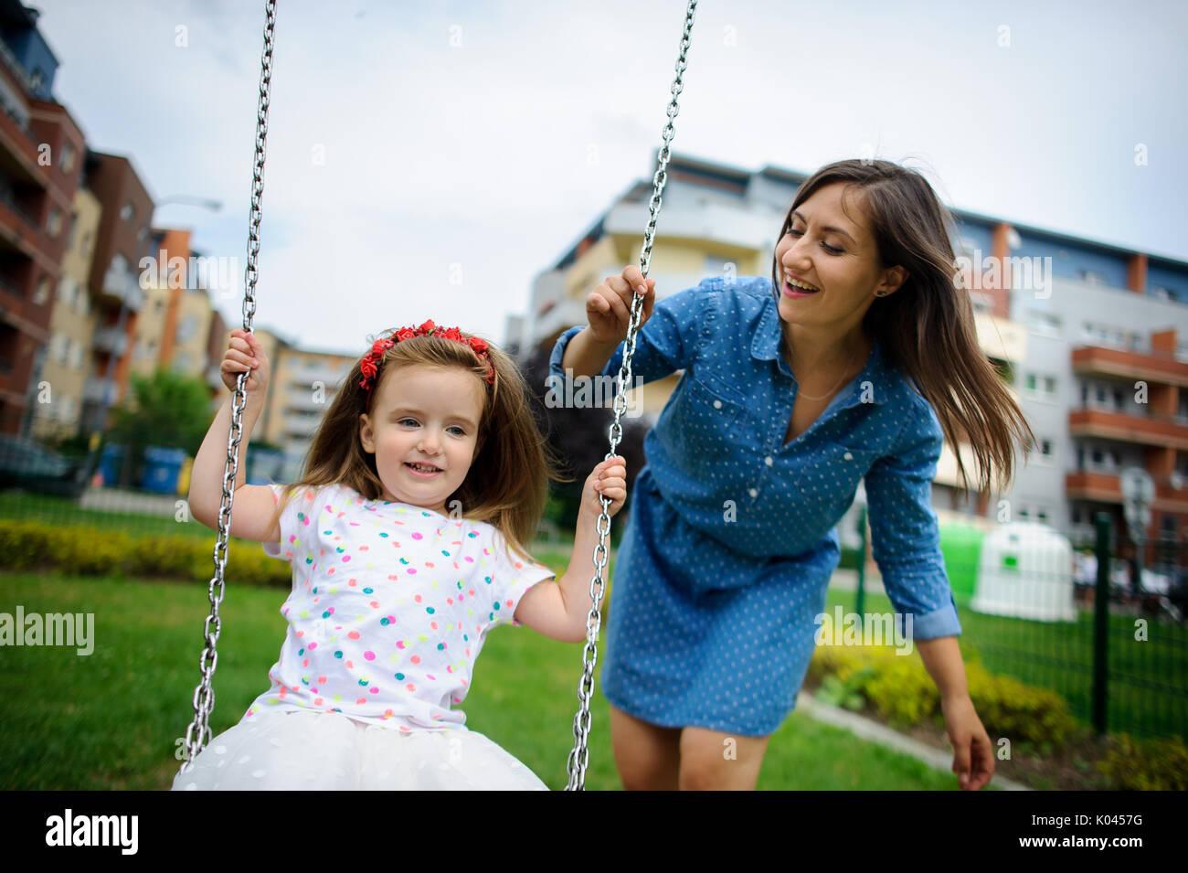 Jeune mère joue dans l'aire de jeux avec la petite fille. Femme secoue le bébé sur une balançoire. Cour de la ville. Serene journée d'été. Bonne humeur. Photo Stock