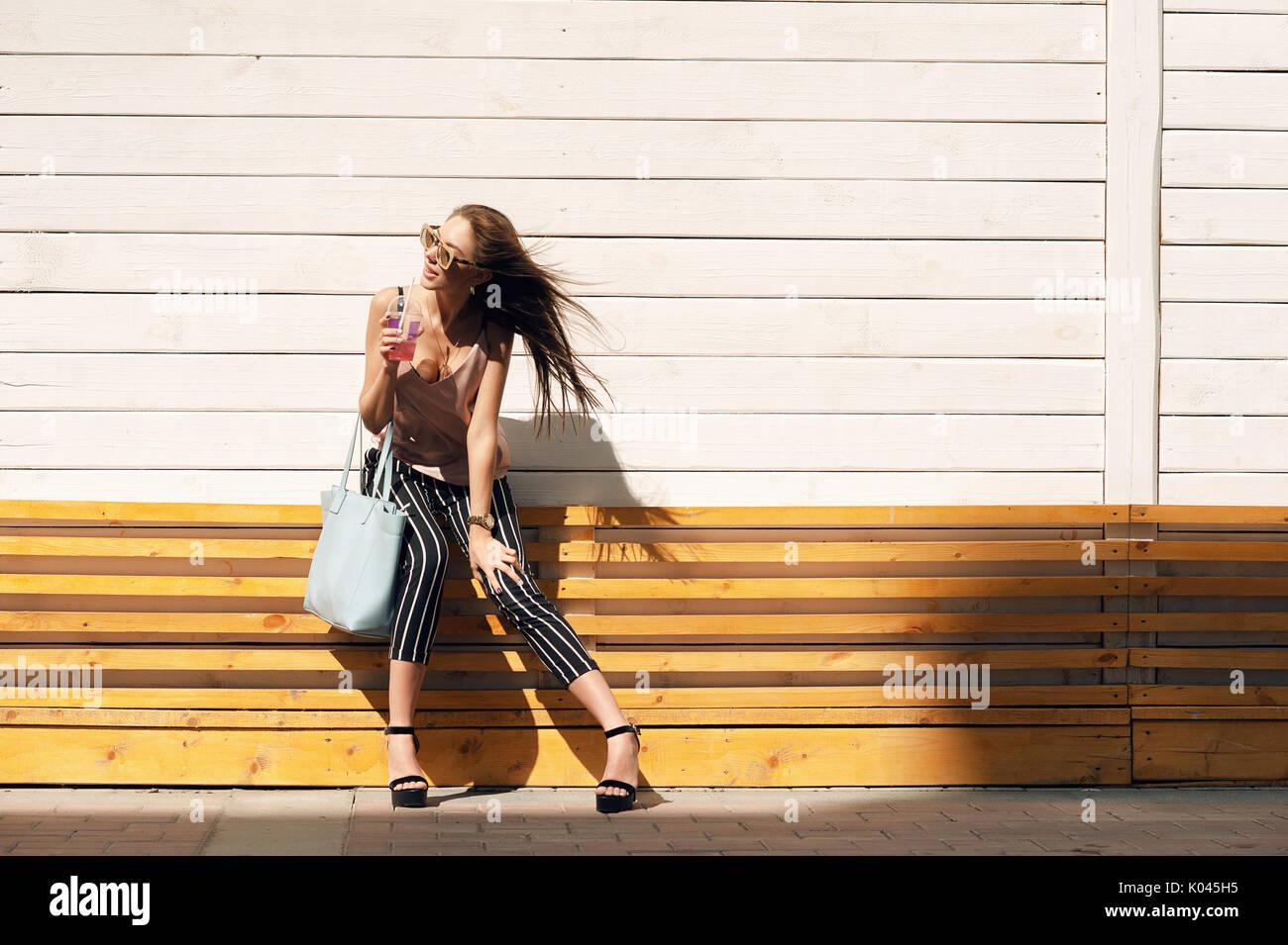Portrait de l extérieur une belle jeune femme portant des lunettes de  sécurité avec une assurance à la mode, dans un cadre en bois, contre un mur  blanc, ... e943b5fd8d3f