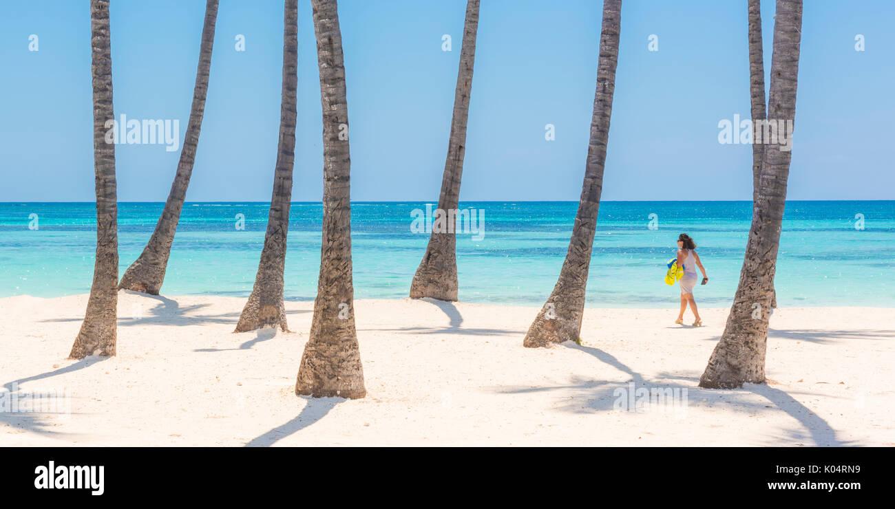 Juanillo Beach (playa Juanillo), Punta Cana, République dominicaine. Femme marche sur la plage bordée de palmiers Banque D'Images