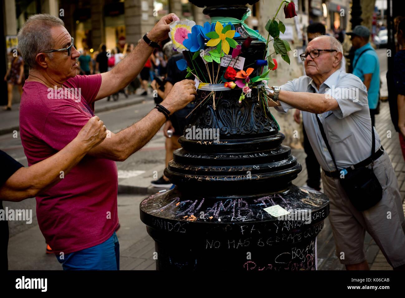 Barcelone, Espagne. Août 21, 2017. Deux hommes place fleurs à un lampadaire de Las Ramblas de Barcelone, en mémoire de l'attaque terroriste aux victimes le même jour que Younes Abouyaaqoub, identifiés comme chauffeur de van qui a accéléré le long de la rue Las Ramblas le jeudi, a été abattu par des agents de police catalane dans le village de Subirats. Crédit: Jordi Boixareu/Alamy Live News Banque D'Images