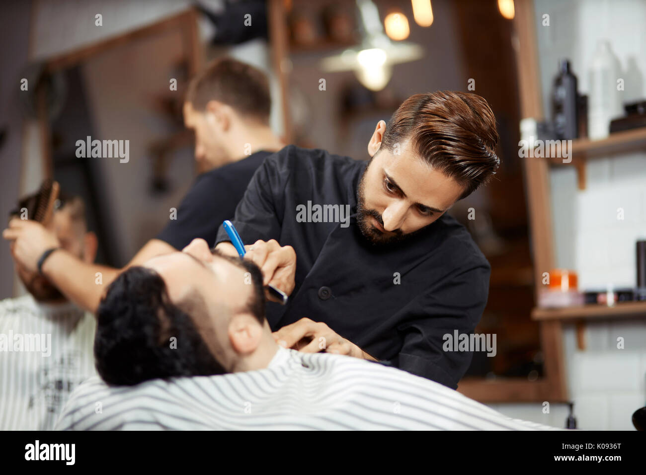 Jeune homme rasage coiffure concentré Photo Stock