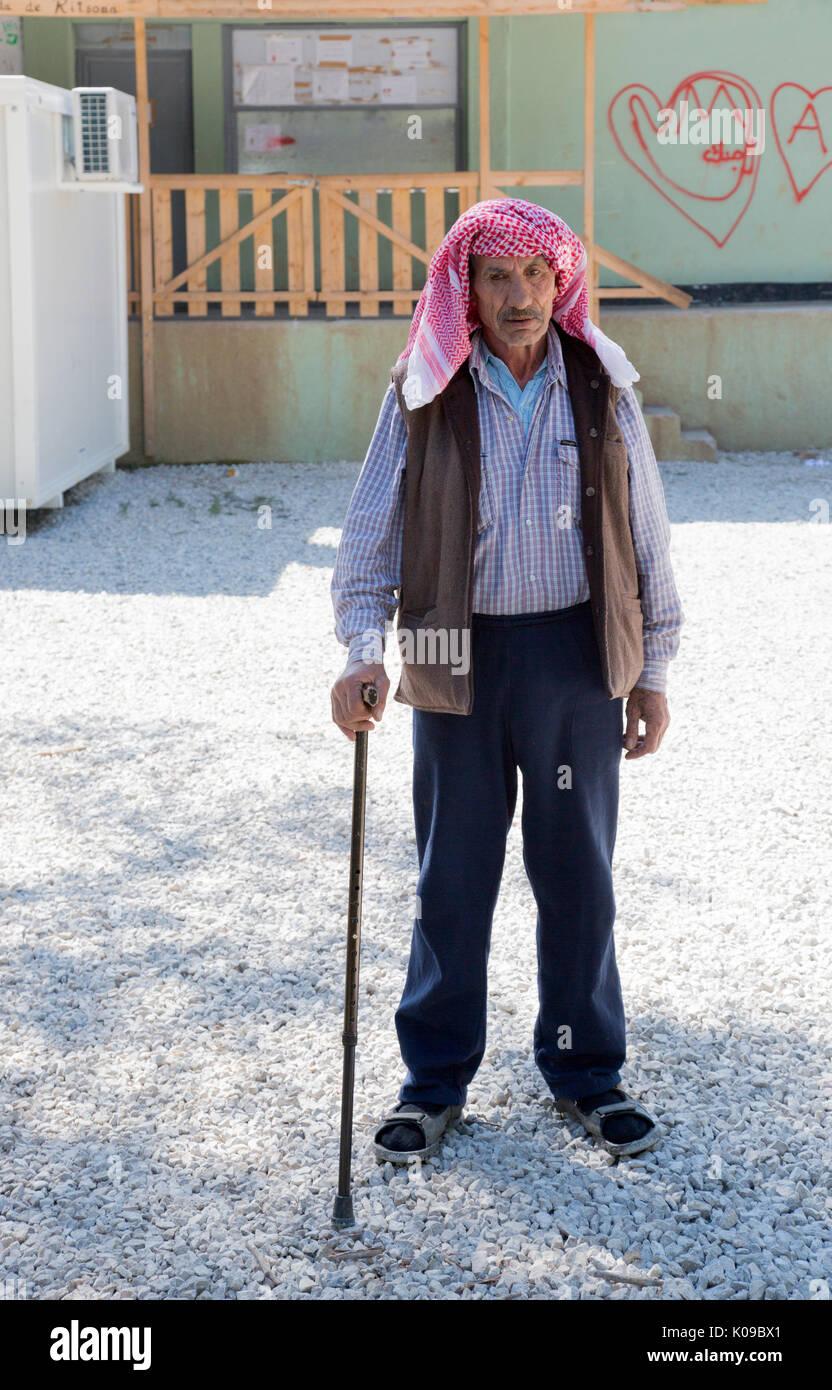 À Ritsona camp de réfugiés pour les Syriens. Un vieil homme syrienne soutenue par un bâton de marche se place en avant d'un bâtiment avec des graffitis. Photo Stock