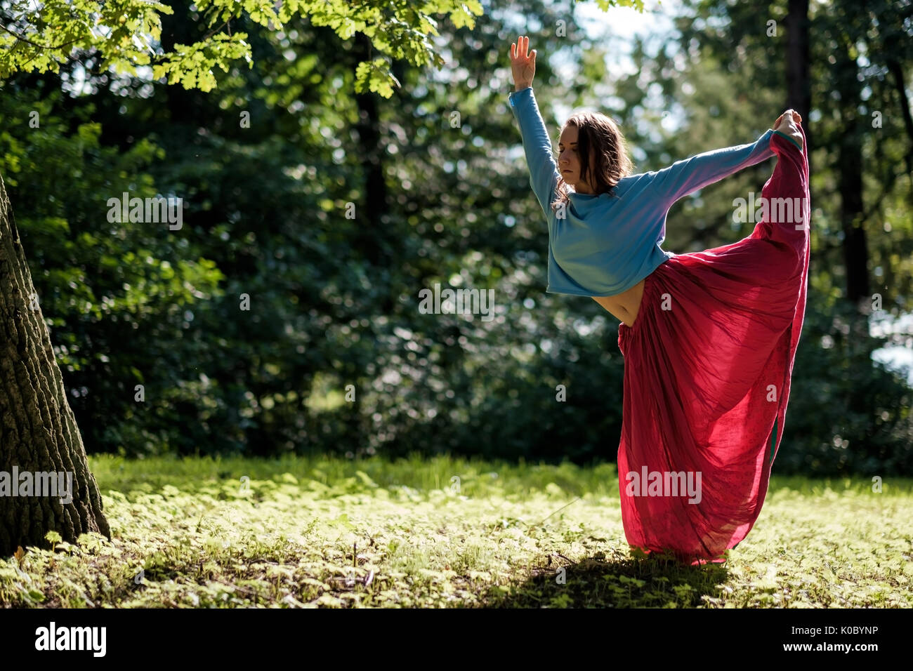 Mettre en place sportive woman faisant l'asana Virabhadrasana 2 guerrier pose posture dans la nature. Photo Stock