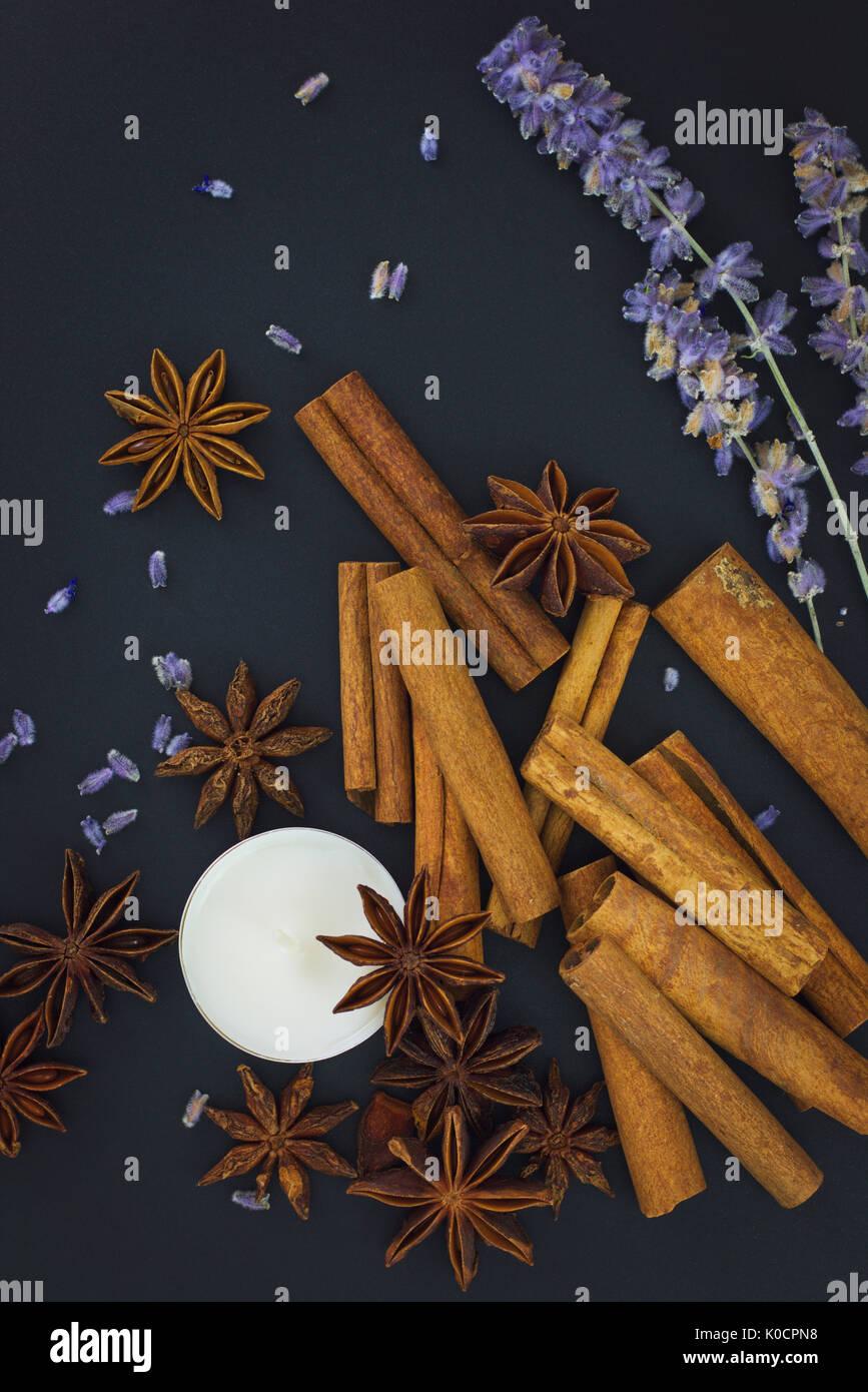Sentiment d'Épices cannelle et anis étoilé avec bougie sur fond noir avec copie espace Photo Stock
