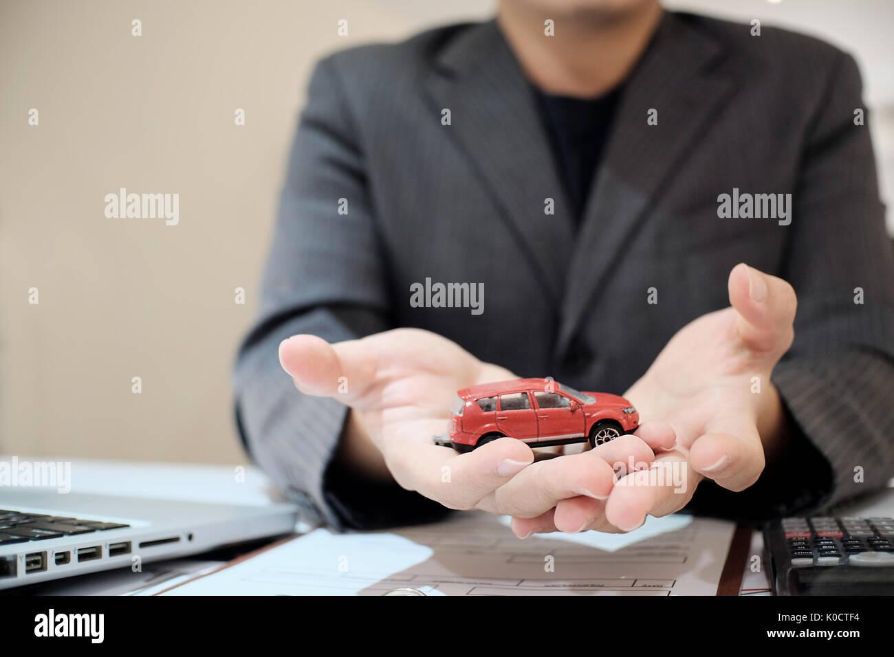 Vendre une voiture d'homme présent dans la salle d'exposition, vente voiture concept. Photo Stock
