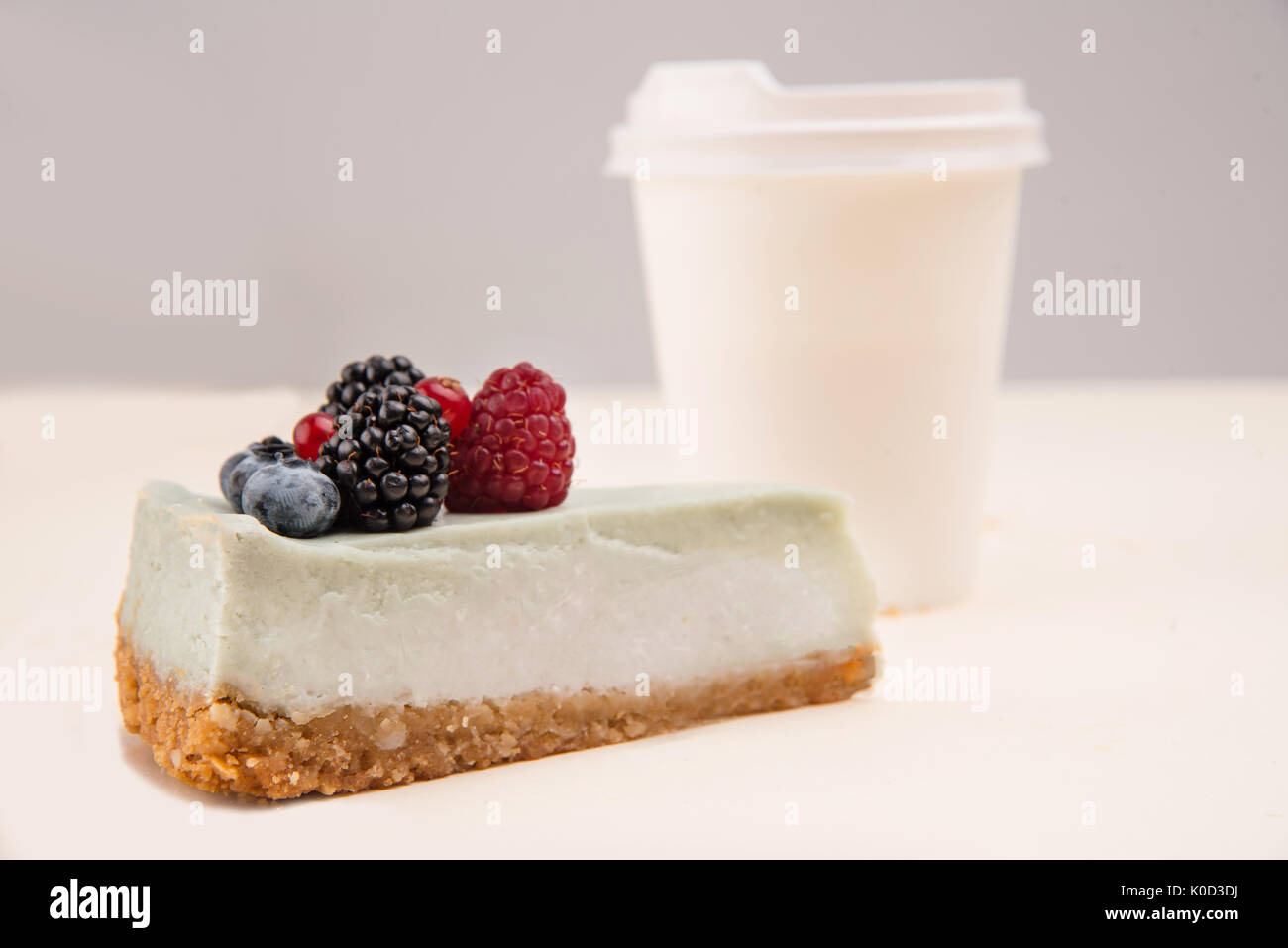 Gâteau au fromage bleu baies wit debout près de tasse de papier isolé Photo Stock