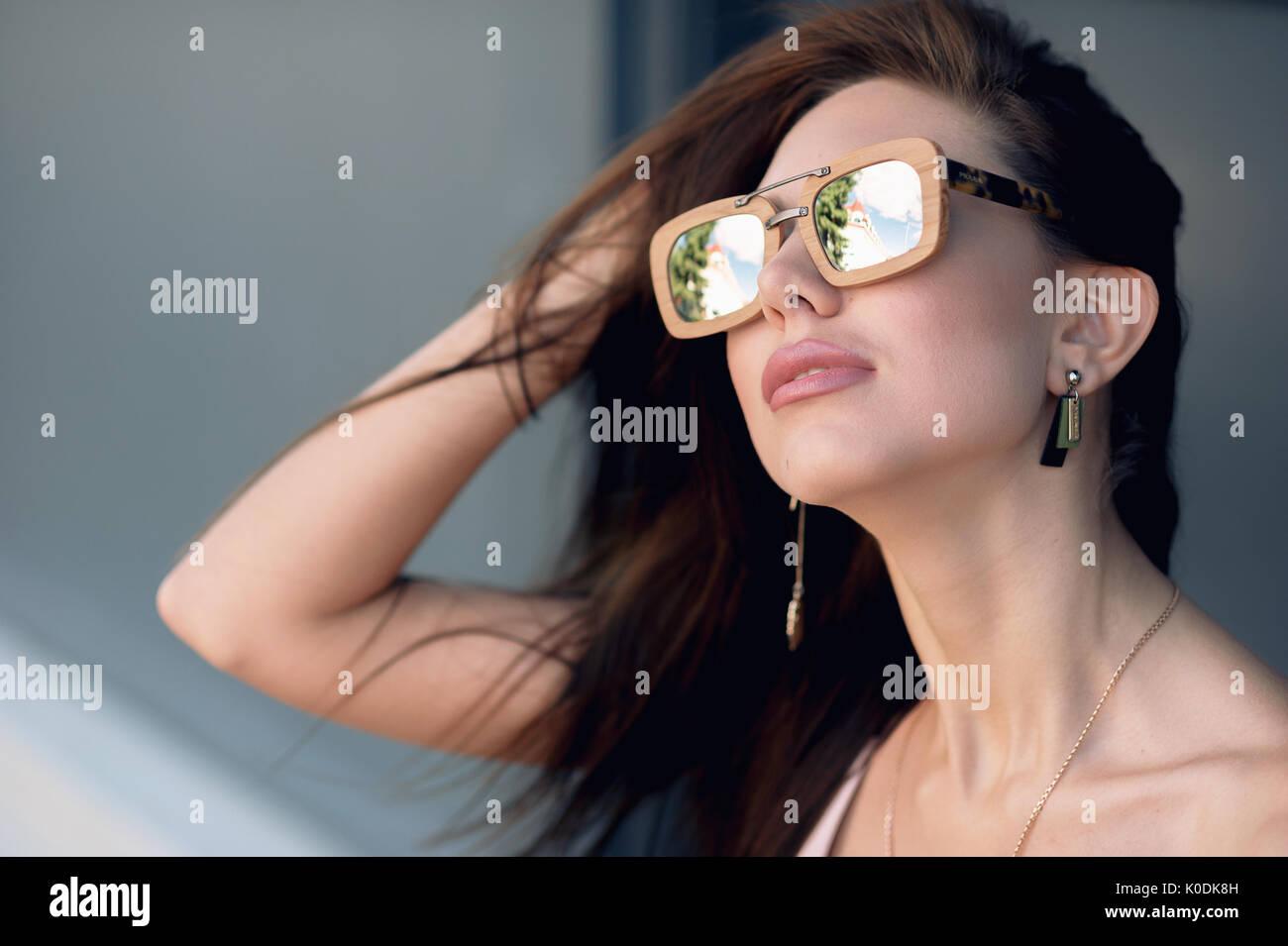 Portrait de l extérieur une belle jeune femme à la mode, heureux, portant  des lunettes de soleil dans un cadre en bois, la création d une ville sur  la rue. 76b241a88672