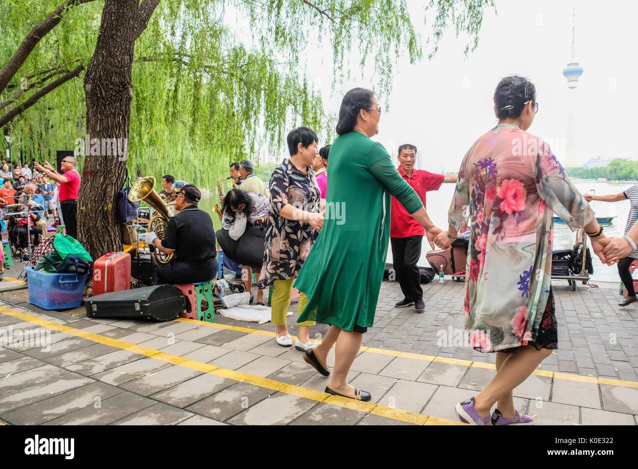 Chinois retraités hommes et femmes pratiquant la danse carrée dans un parc Photo Stock