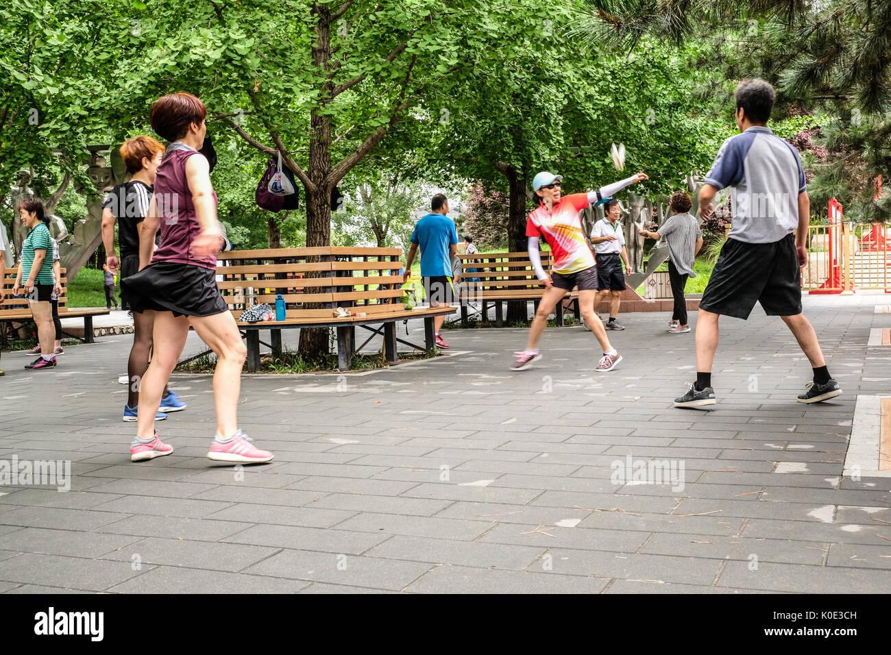 Un groupe d'hommes et de femmes chinoises des coups de volant dans le parc Photo Stock