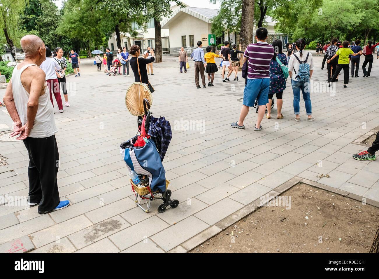 Les hommes et les femmes retraités chinois pratiquant la danse latine à un parc public, avec un homme âgé dans et vieille fashion shirt à la recherche sur. Photo Stock