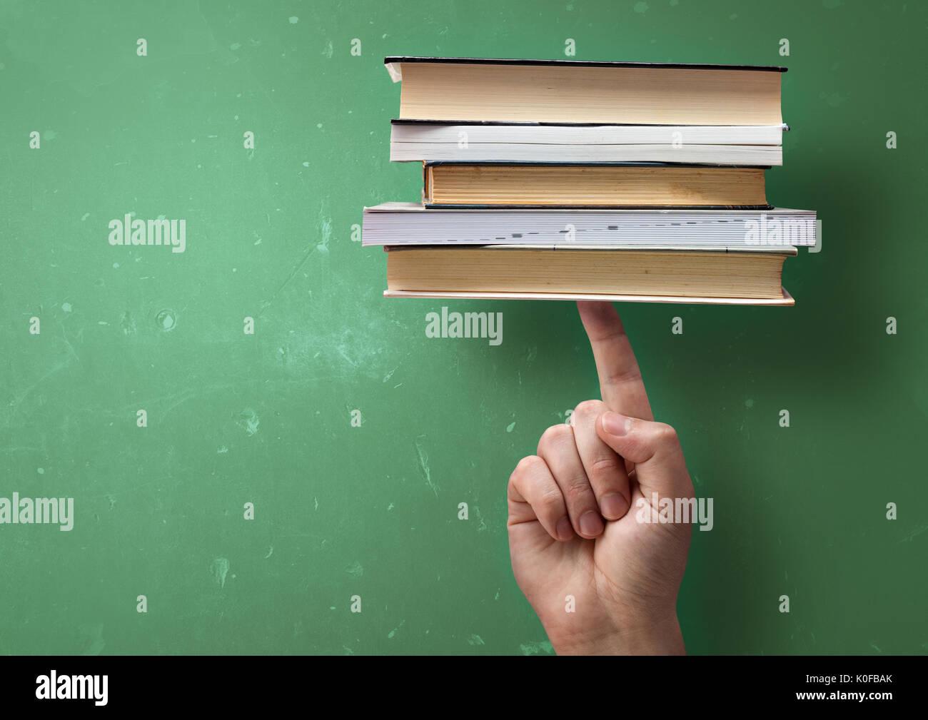 Un student holding up livres d'études d'un seul doigt. La réussite de l'apprentissage rapide concept. Photo Stock