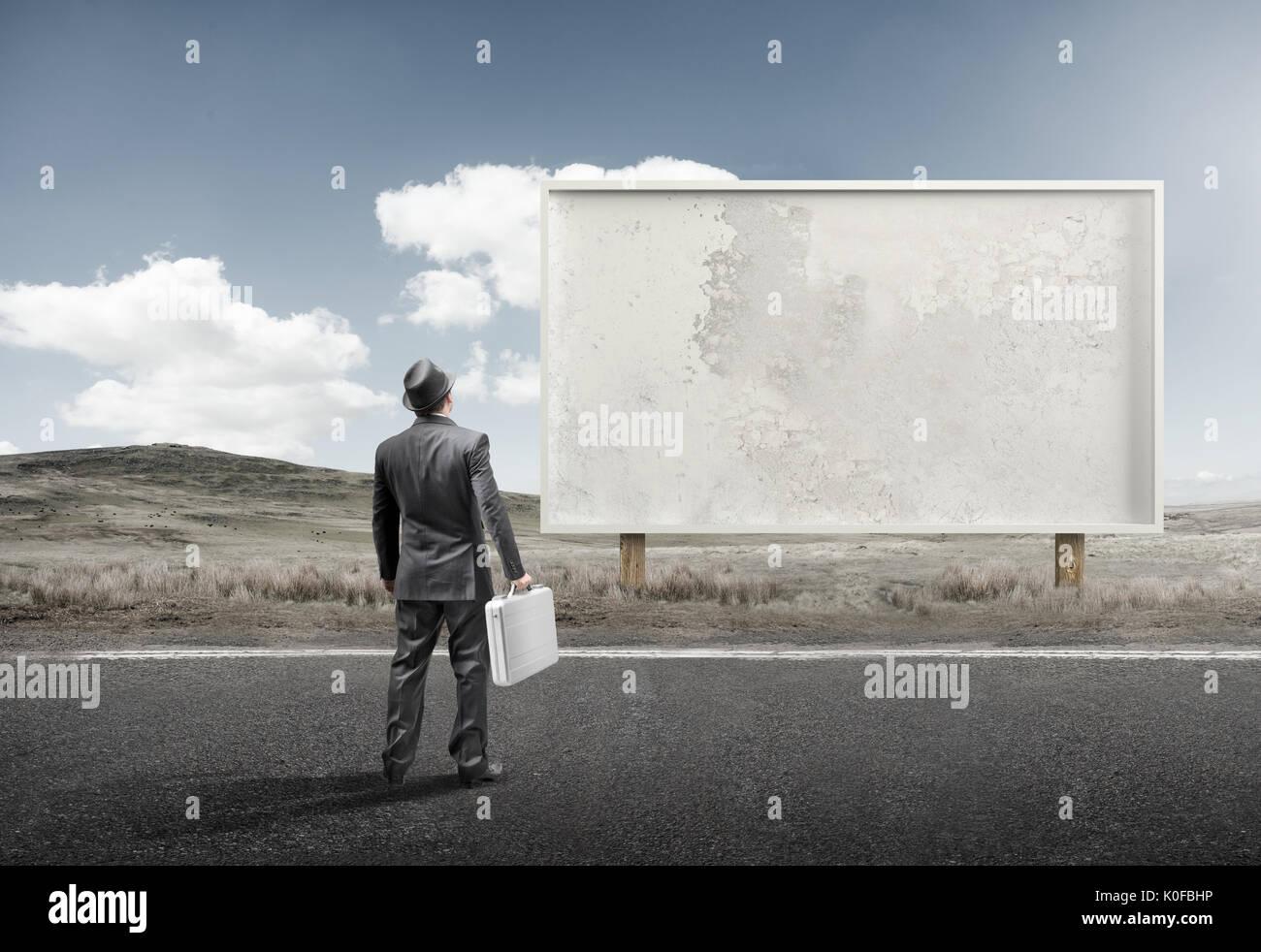 Un homme d'affaires et commandes devant un panneau d'affichage vierge. Photo Stock