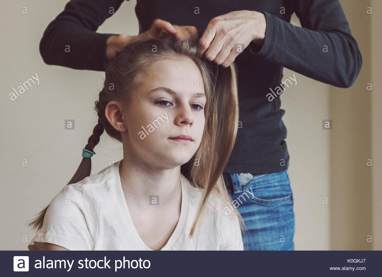 Tressage de cheveux de la mère des jeunes filles. Portrait de la vie réelle de blancs photo teen girl avec filtre mate chaud délibérée Photo Stock
