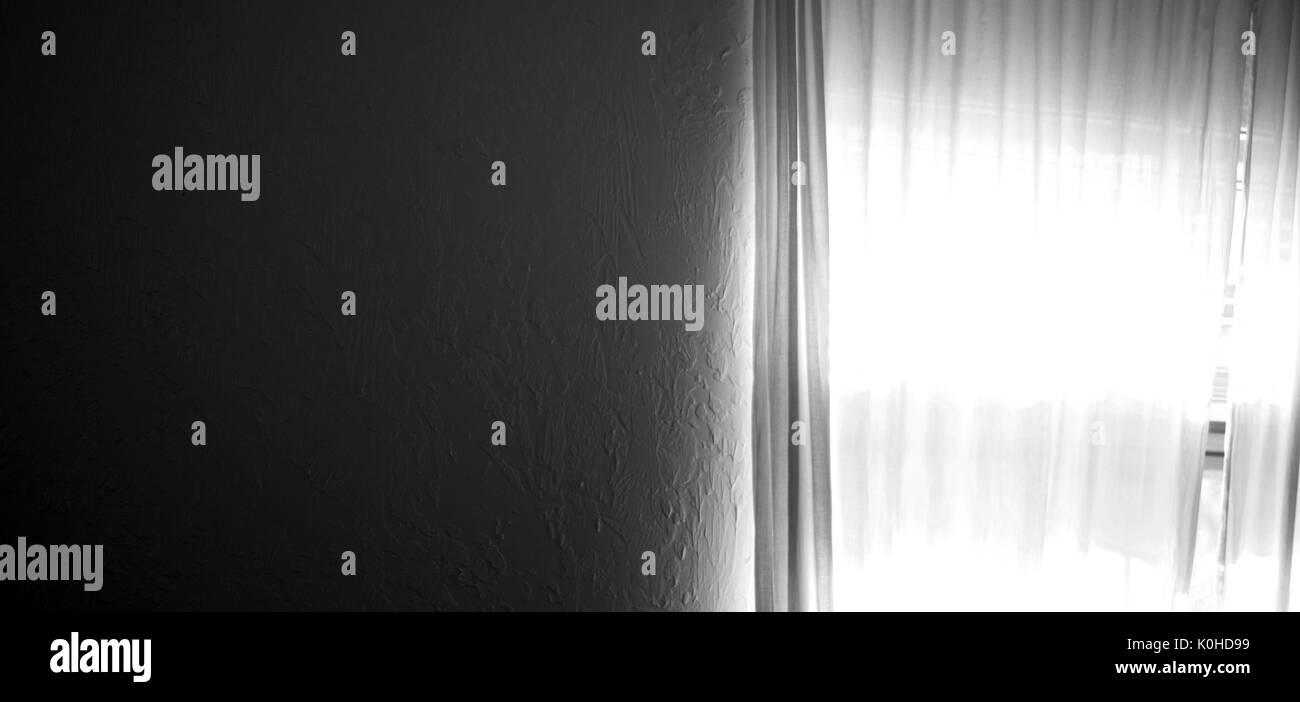 Un mur texturé Blanc foncé remplit la moitié de l'image et à droite est une fenêtre avec des rideaux à la lumière du soleil qui brillait à travers, rideaux opaques. Photo Stock