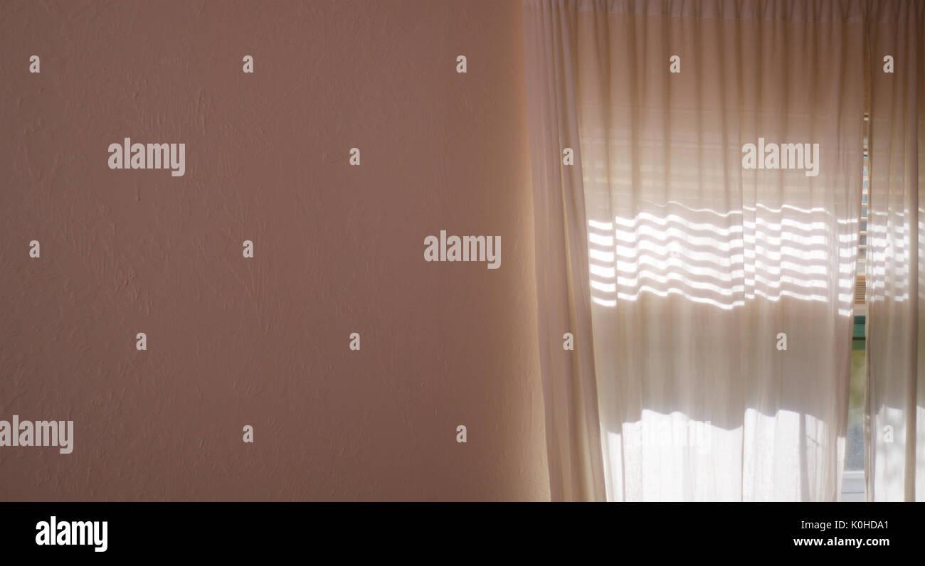 Un mur texturé intérieur blanc se remplit la moitié de l'image et à droite est une fenêtre avec des rideaux du soleil brillant à travers, rideaux opaques. Photo Stock